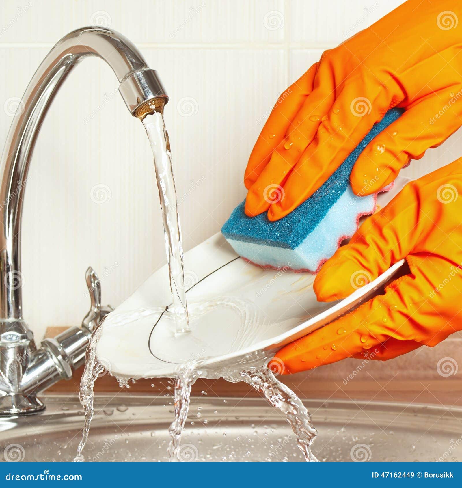 les mains dans les gants en caoutchouc font la vaisselle sale sous l 39 eau courante dans la. Black Bedroom Furniture Sets. Home Design Ideas