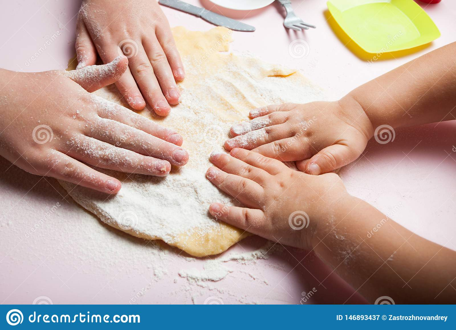 Les mains de bébé malaxent la pâte, plan rapproché