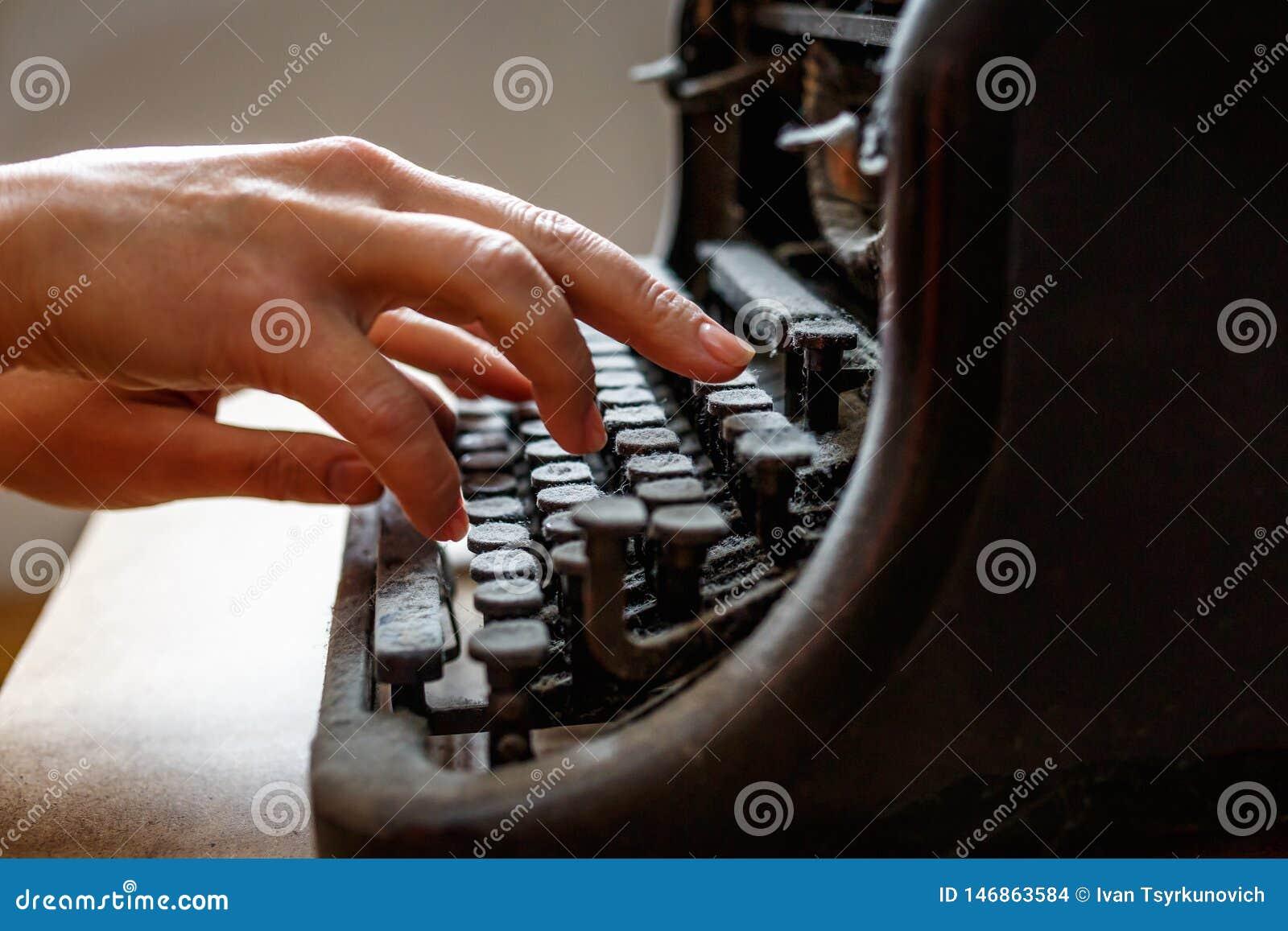Les mains de femme dactylographient sur une machine à écrire couverte de poussière de vieux cru