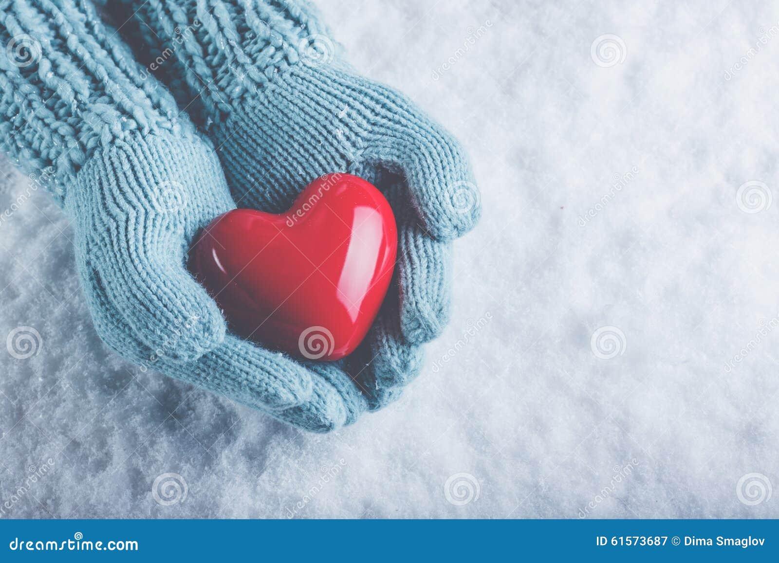 Les mains de femme dans des mitaines tricotées par sarcelle d hiver légère tiennent le beau coeur rouge brillant à l arrière-plan