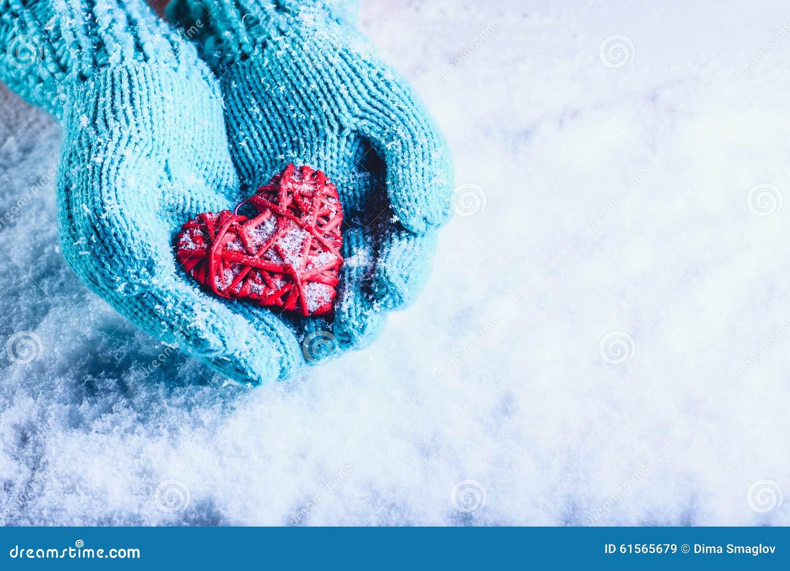 Les mains de femme dans des mitaines tricotées par sarcelle d hiver légère tiennent le beau coeur rouge enlacé de vintage dans un