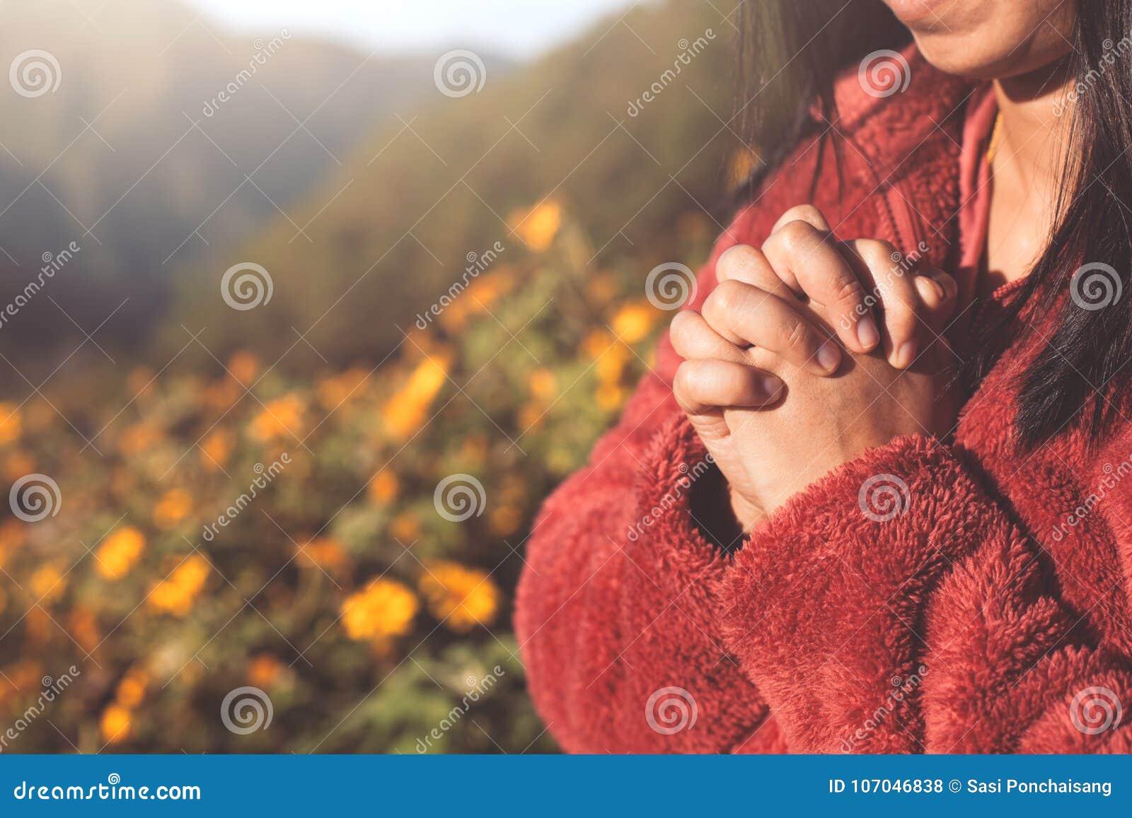 Les mains de femme se sont pliées dans la prière au bel arrière-plan de nature