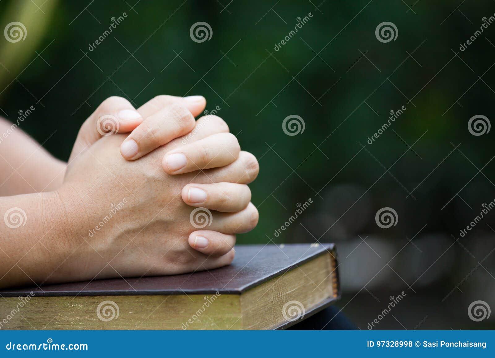 Les mains de femme se sont pliées dans la prière sur une Sainte Bible pour le concept de foi