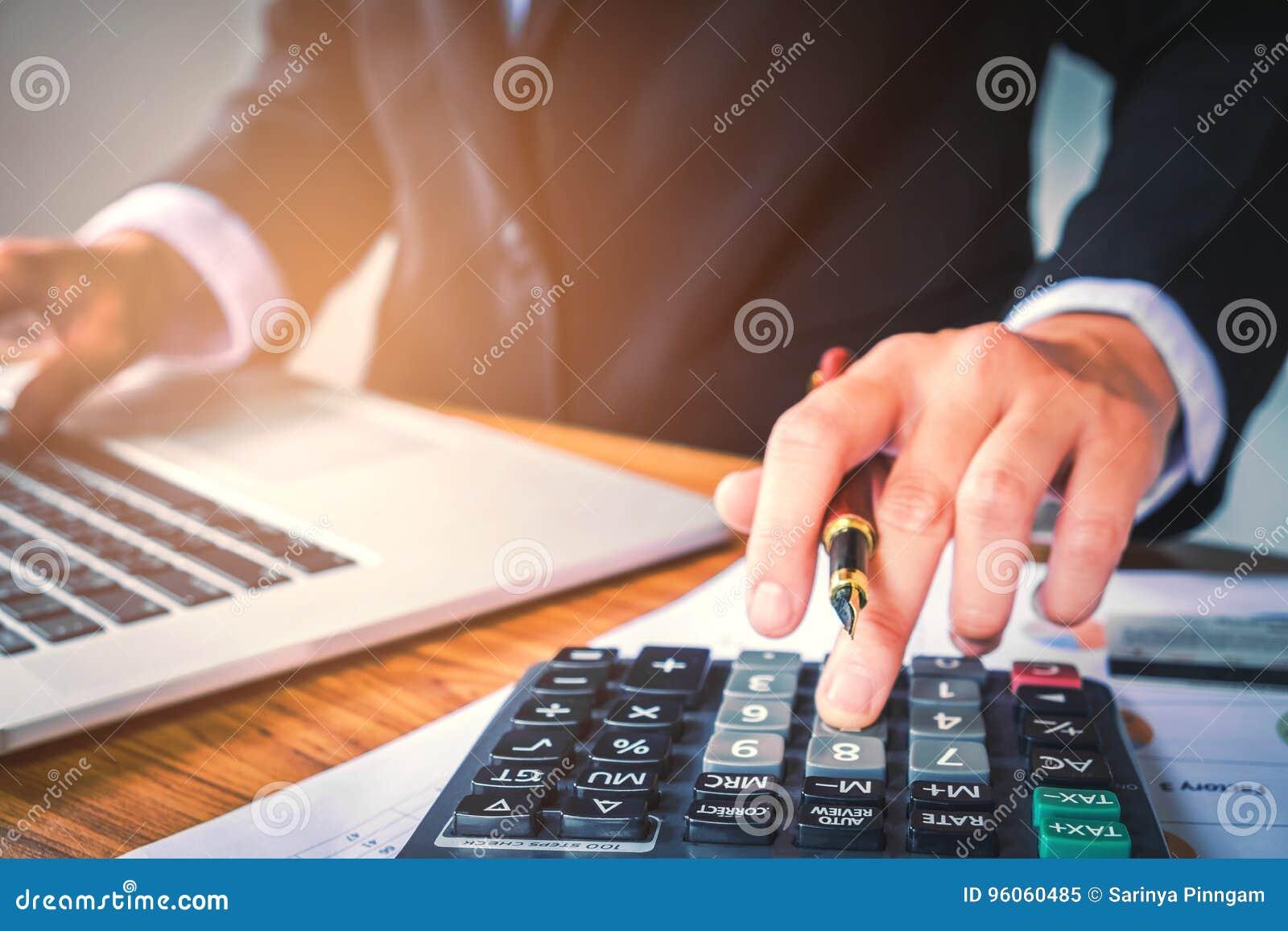 Les mains de l homme d affaires avec la calculatrice au bureau et financier