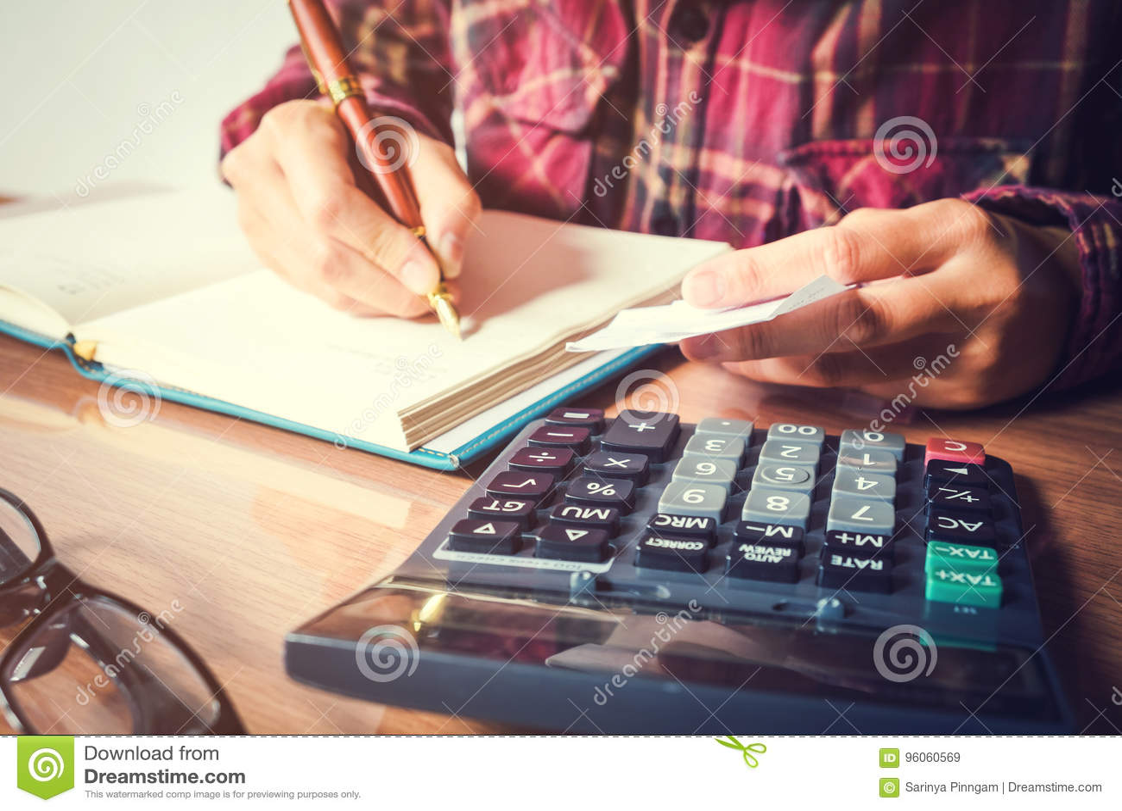 Les mains de l homme d affaires avec la calculatrice comptant faisant des notes au hom
