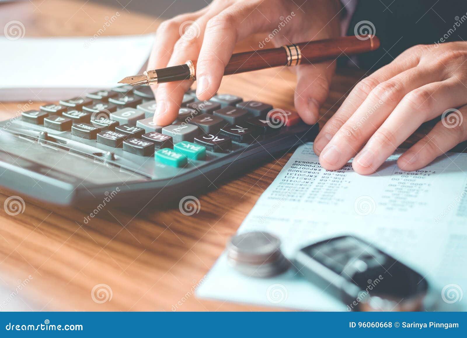 Les mains de l homme d affaires avec la calculatrice et le coût au bureau et au F