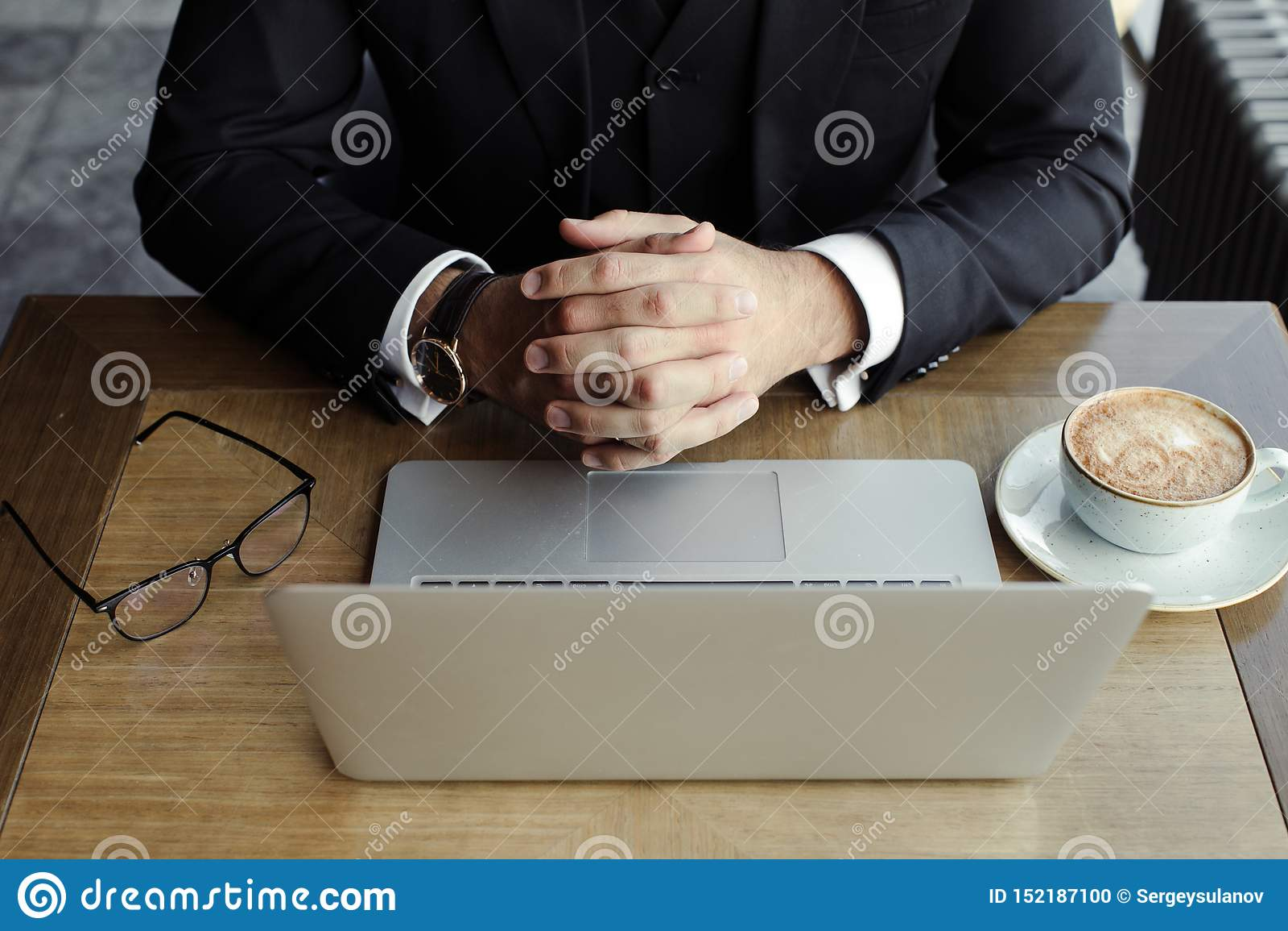 Les mains de l homme sur la table avec l ordinateur portable, le téléphone, le café et les verres