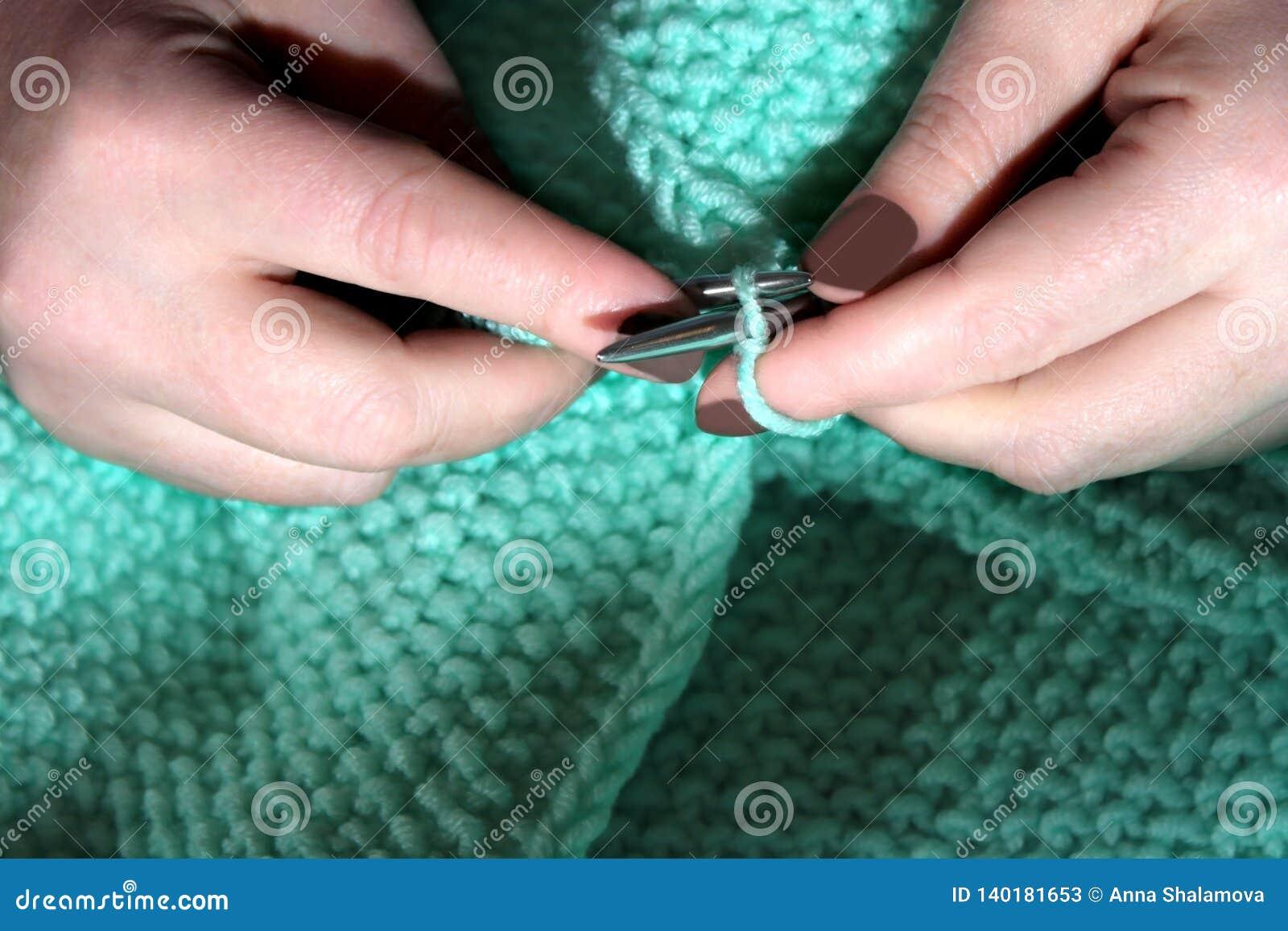 Les mains de la femme avec la manucure, qui tricotent doucement un chandail de turquoise avec les aiguilles de tricotage en acier