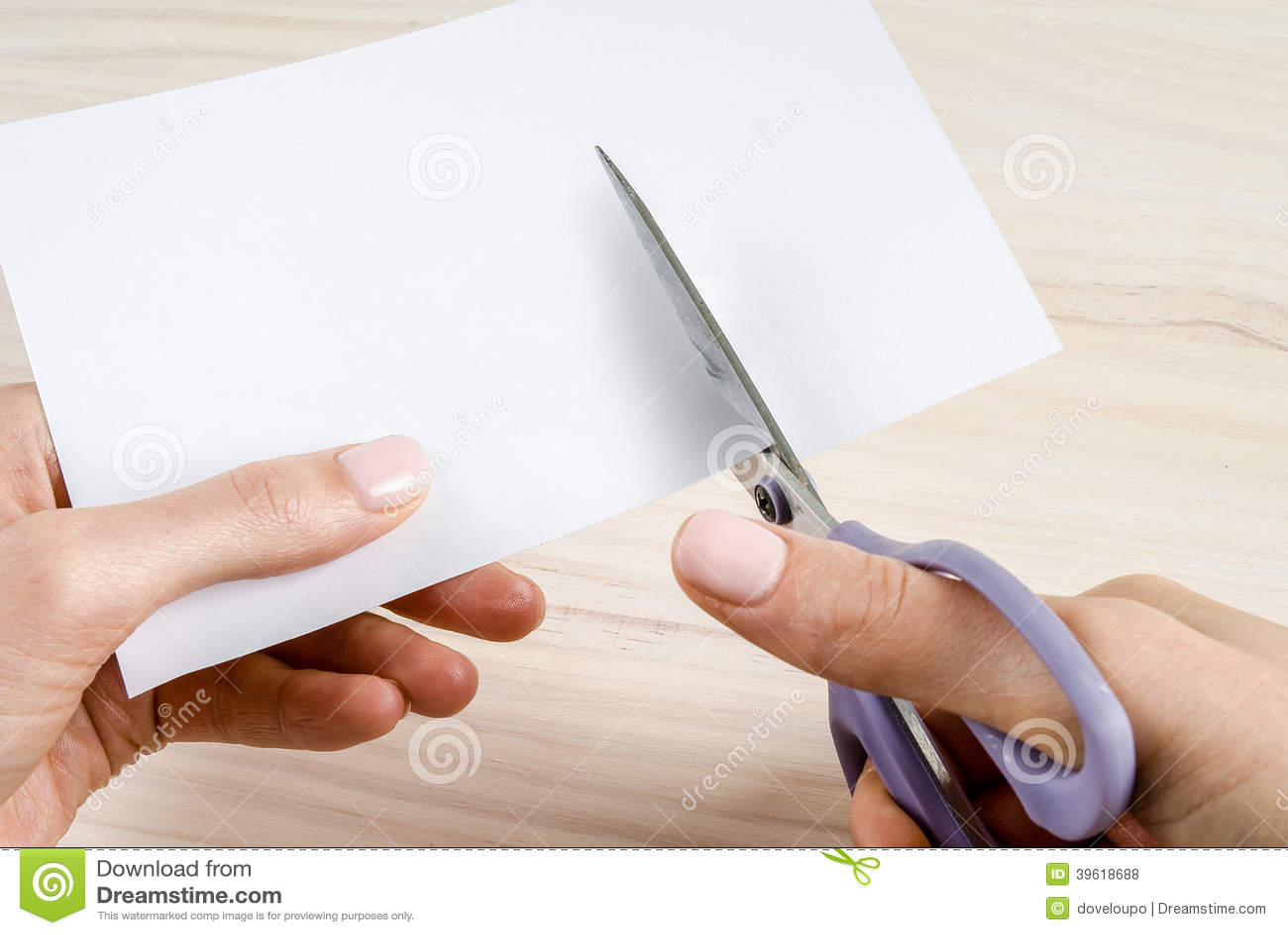 Les mains de la femme coupant le papier avec des ciseaux