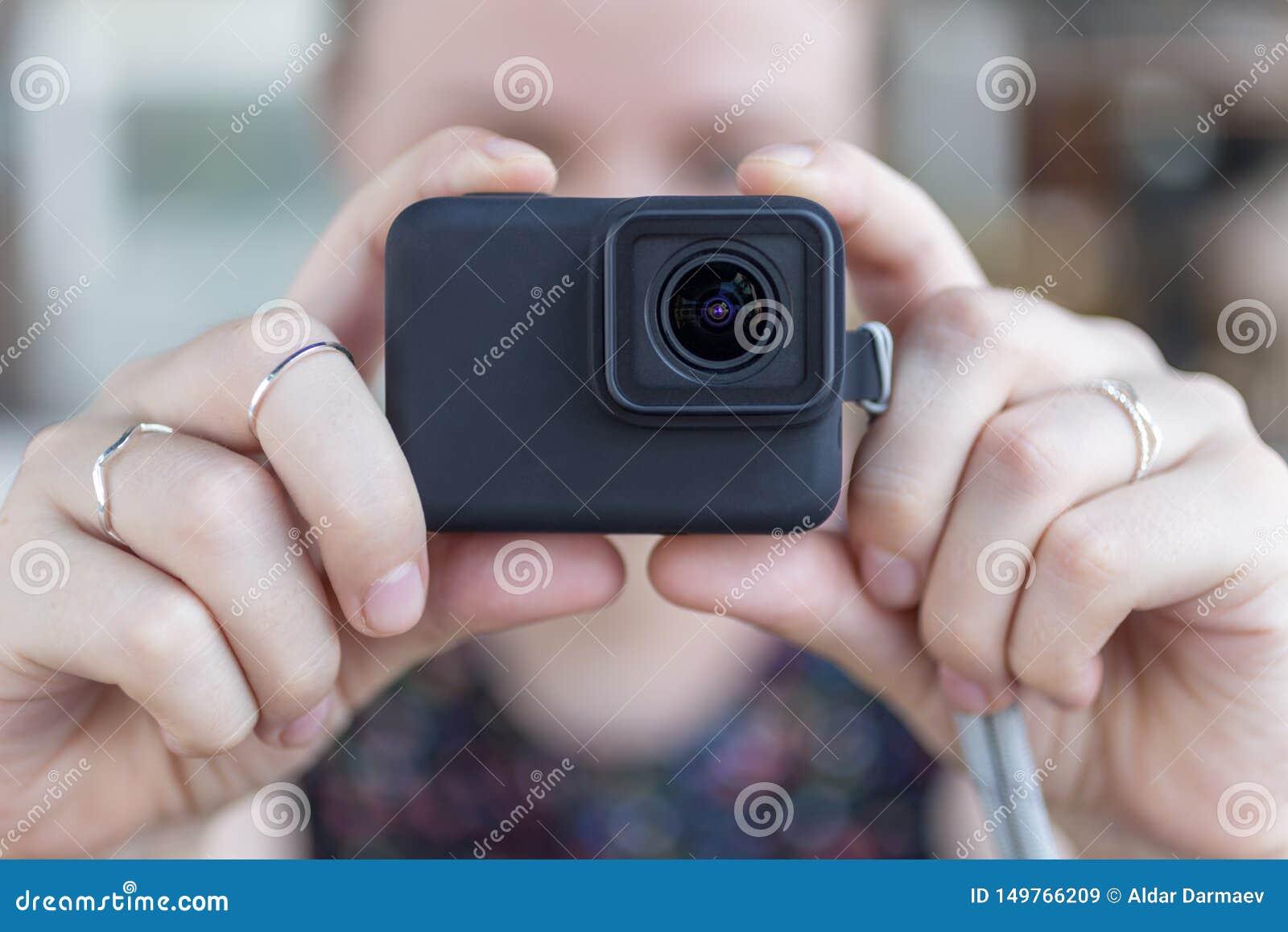 Les mains de la femme se ferment vers le haut de tenir une petite caméra noire d action prenant une vidéo ou une photo