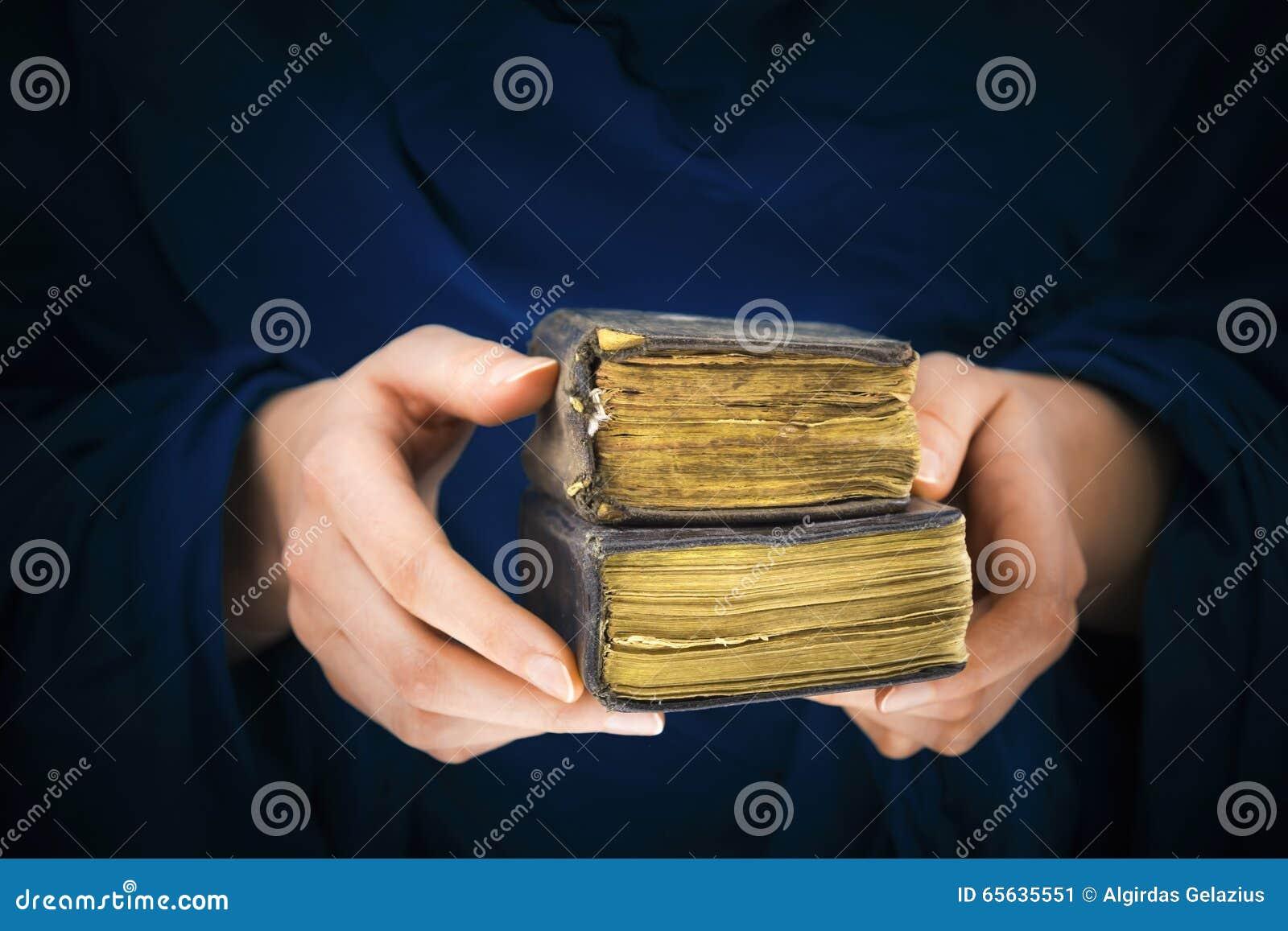 Les mains de la femme tenant deux vieux livres