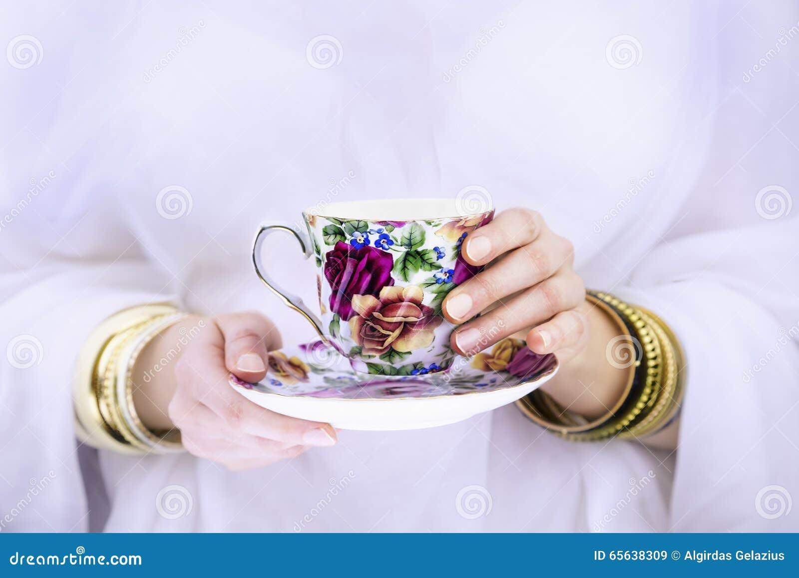 Les mains de la fille avec des bracelets tenant une tasse colorée