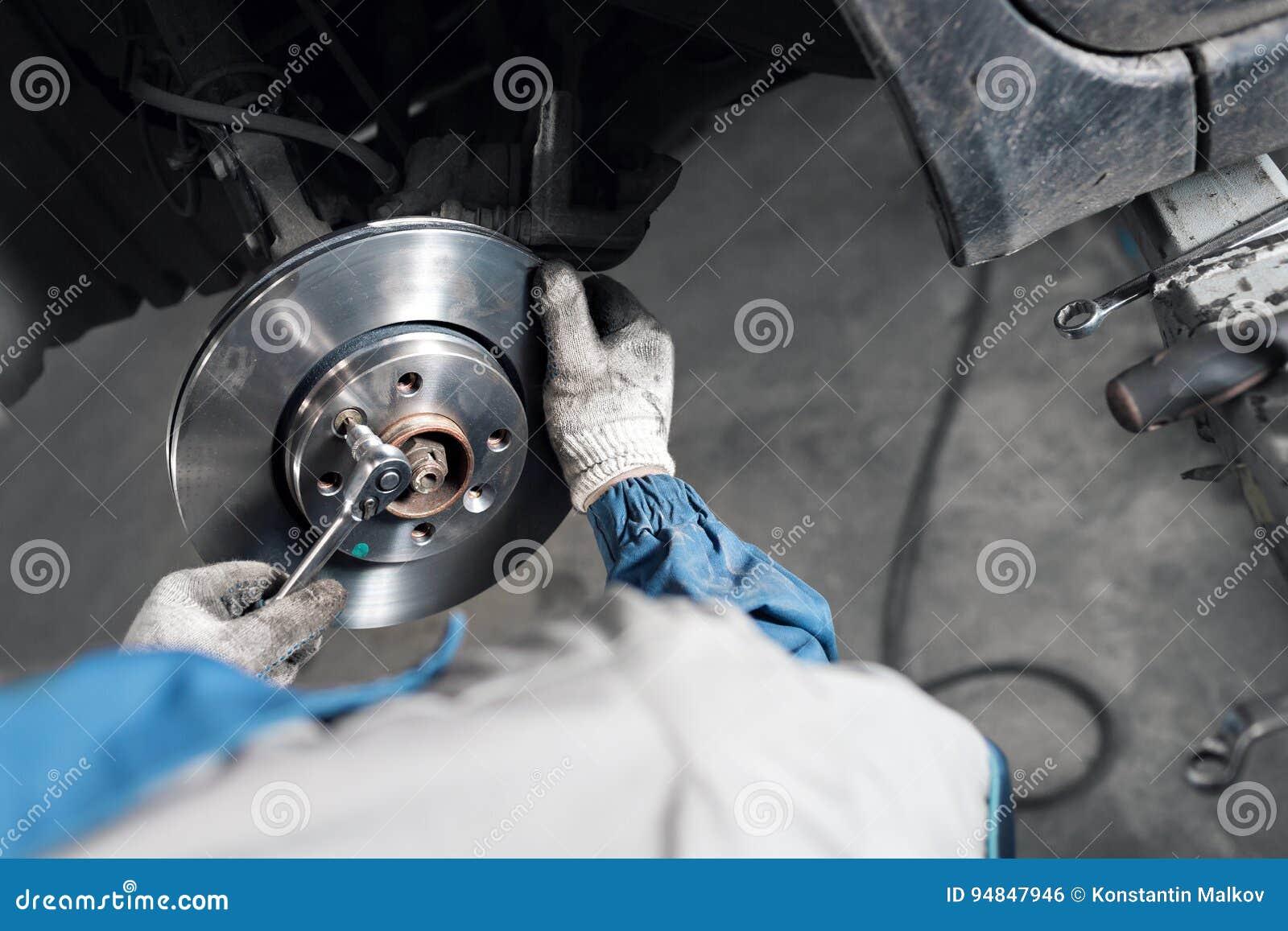 Les mains de mécanicien de voiture remplacent des freins dans le garage