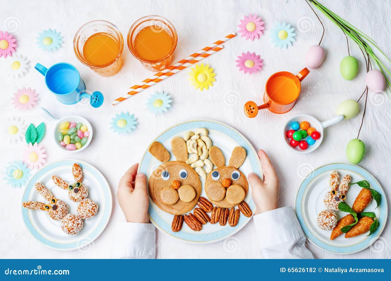 Les mains des enfants avec des crêpes, des bonbons et le jus pour Pâques