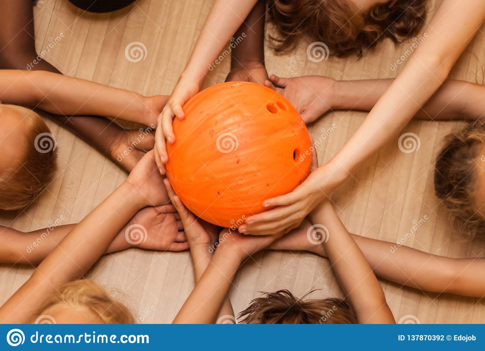 Les mains des enfants de différentes nationalités avec une boule de roulement