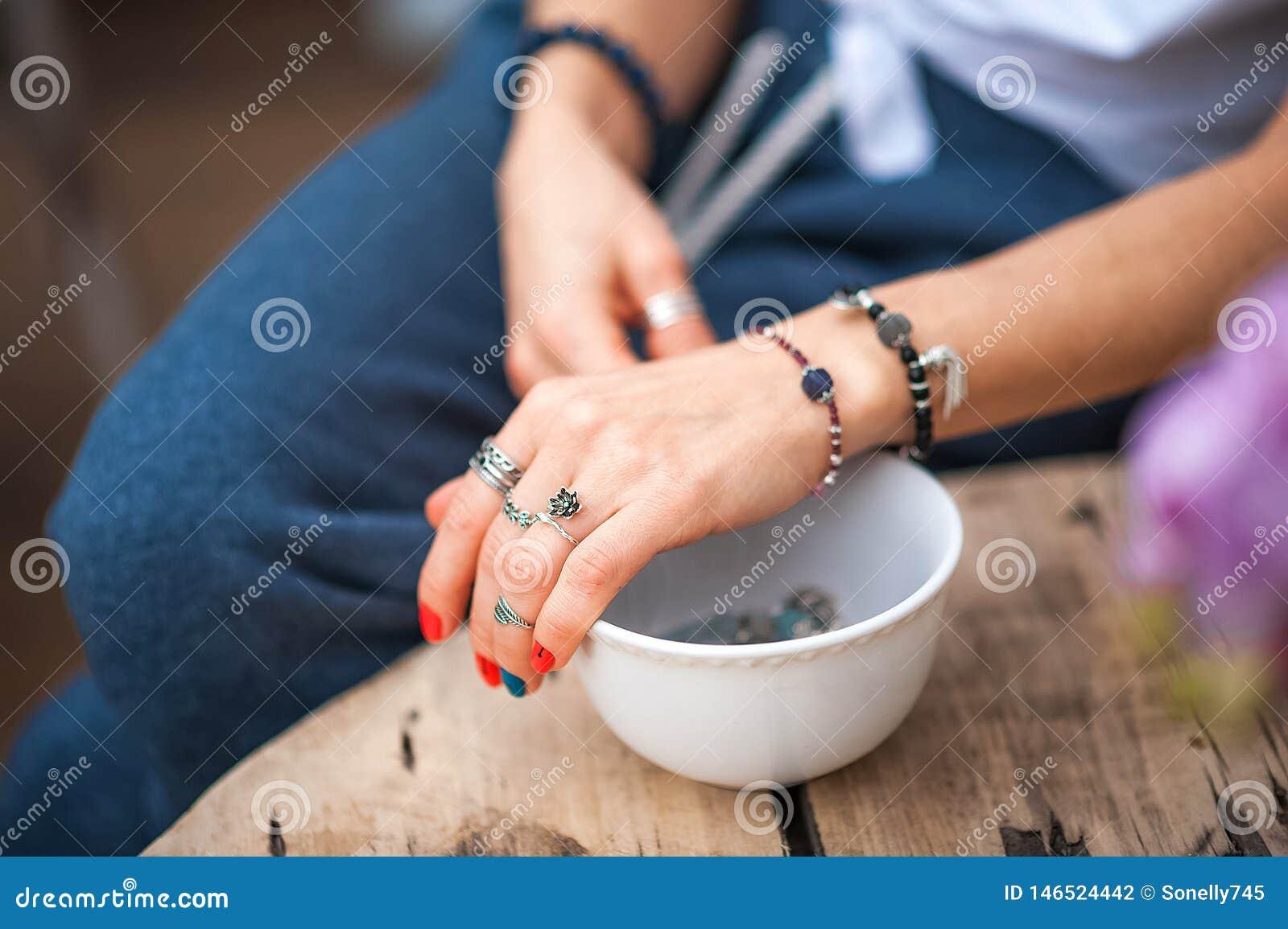 Les mains du contact de fille les bijoux faits main Fille et bijoux La femme faite main d?corant des pierres se ferment
