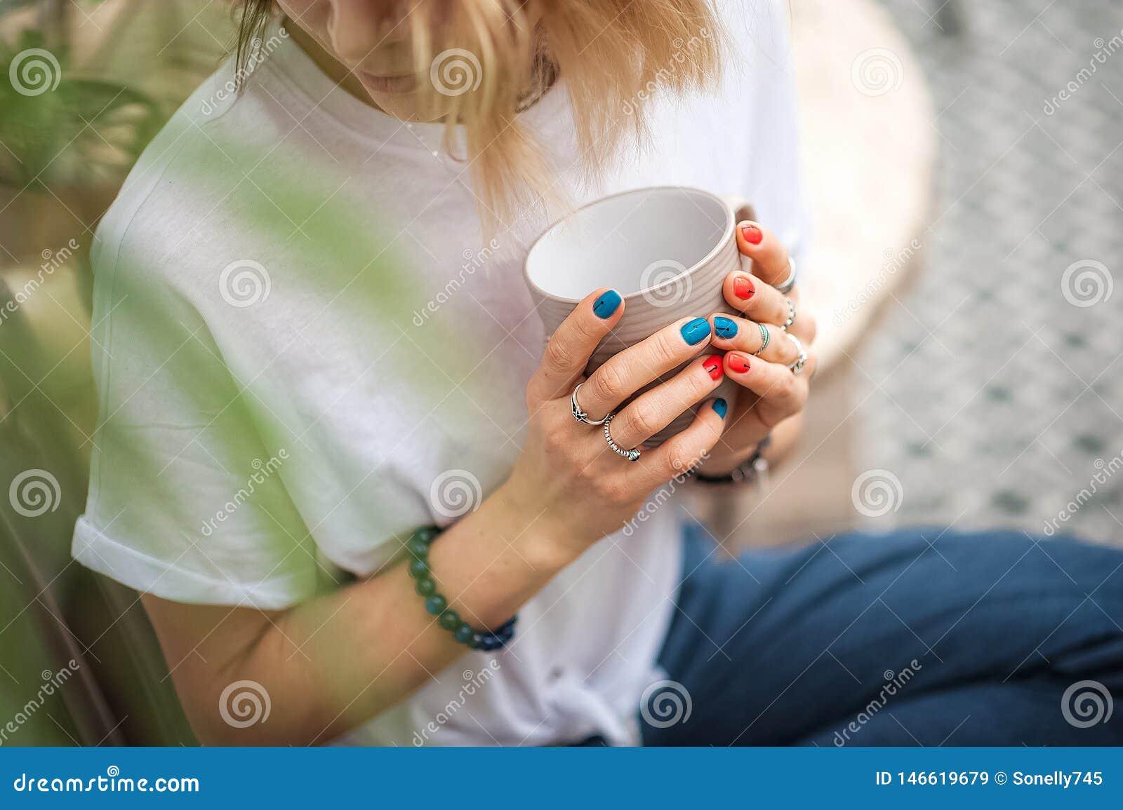 Les mains du contact de fille les bijoux faits main Fille et une tasse Femme faite main décorant des pierres plan rapproché, médi