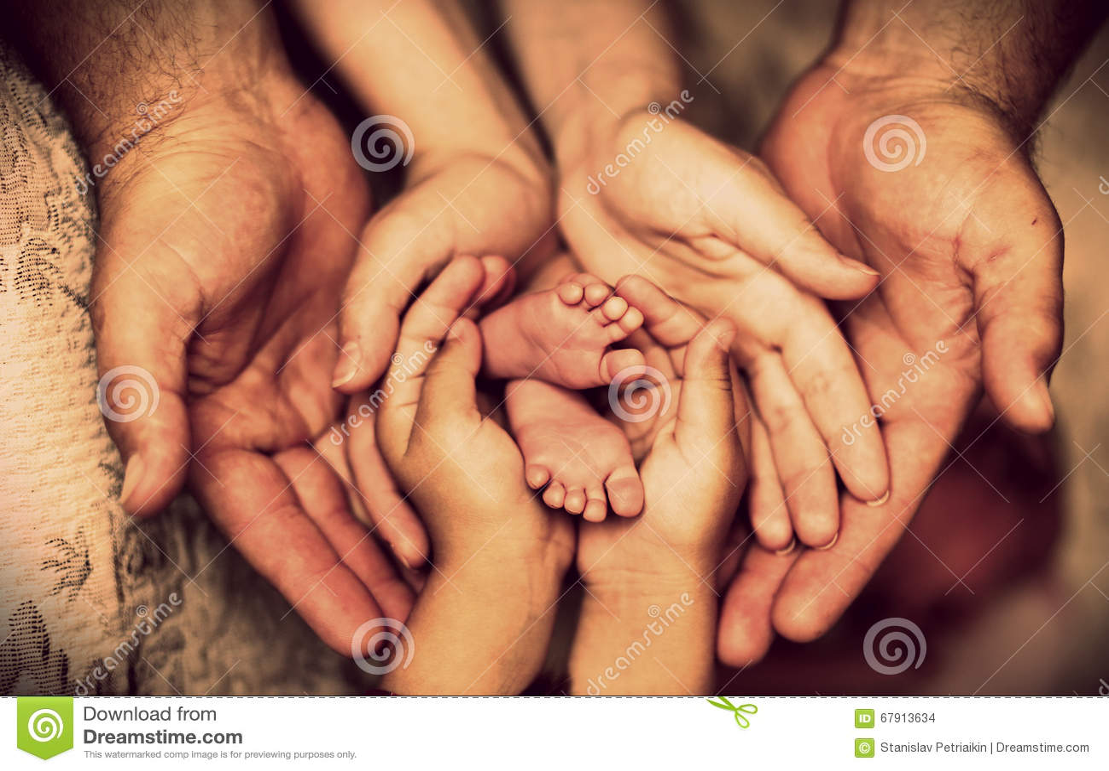 Les mains du père, mère, fille gardent le petit bébé de pieds Famille heureuse amicale