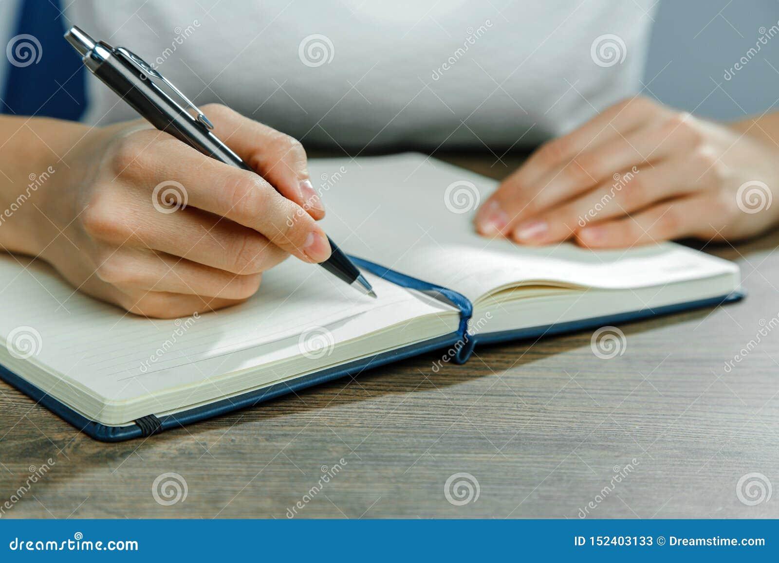 Les mains femelles écrivent dans un carnet