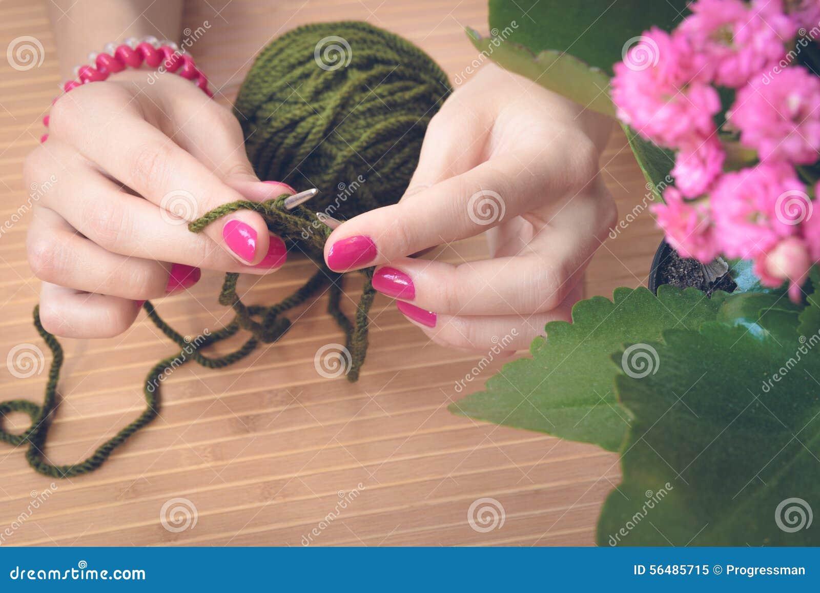 Les mains femelles avec la manucure pourpre sont les rais tricotés en métal d a