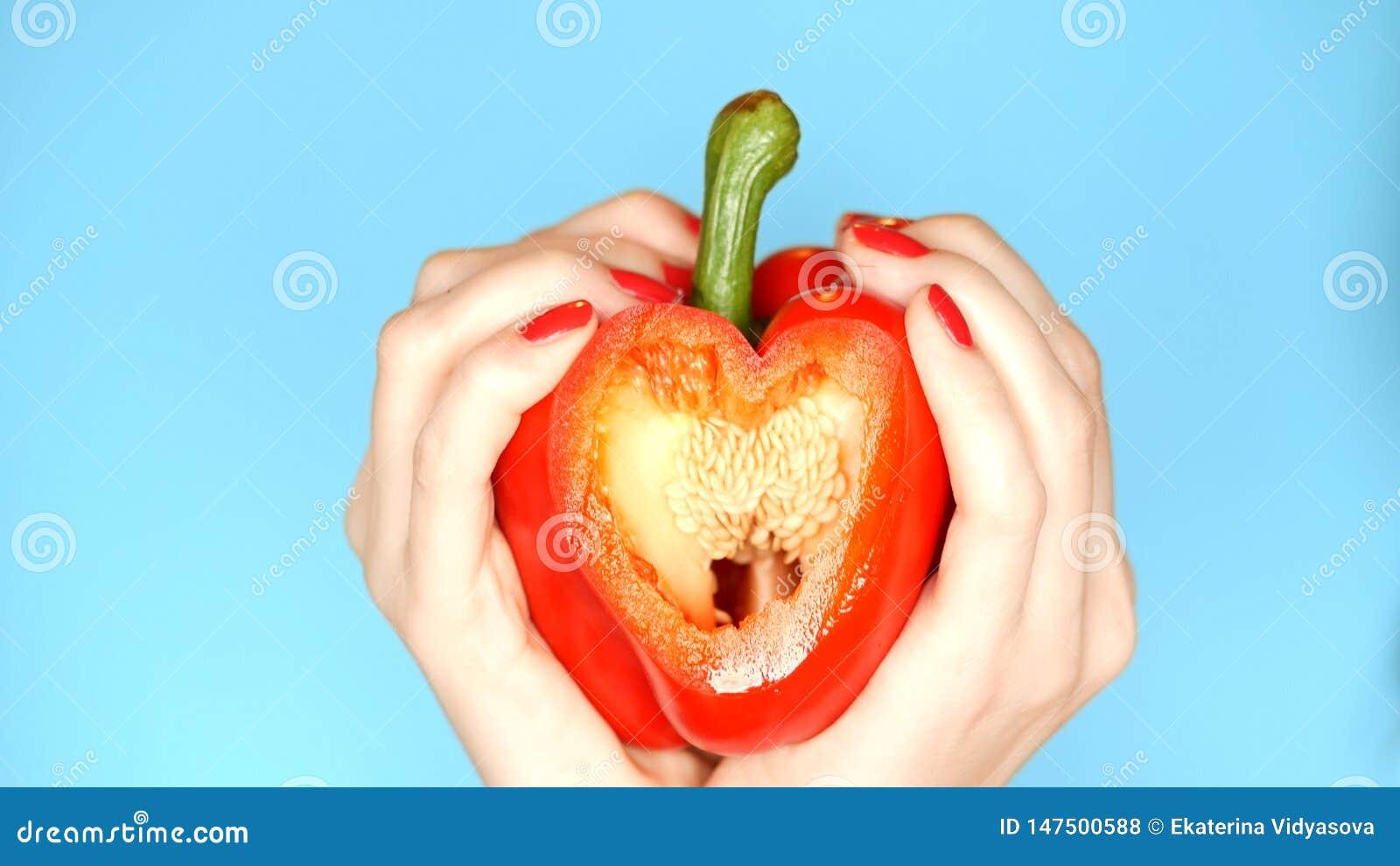 Les mains femelles avec la manucure rouge tiennent le poivron doux rouge ? disposition sous forme de coeur sur un fond bleu