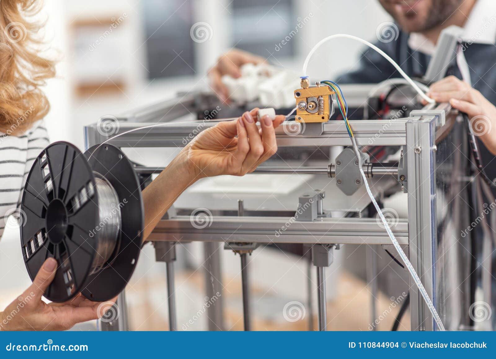Les mains femelles tenant le filament se sont reliées à l extrudeuse de l imprimante 3D