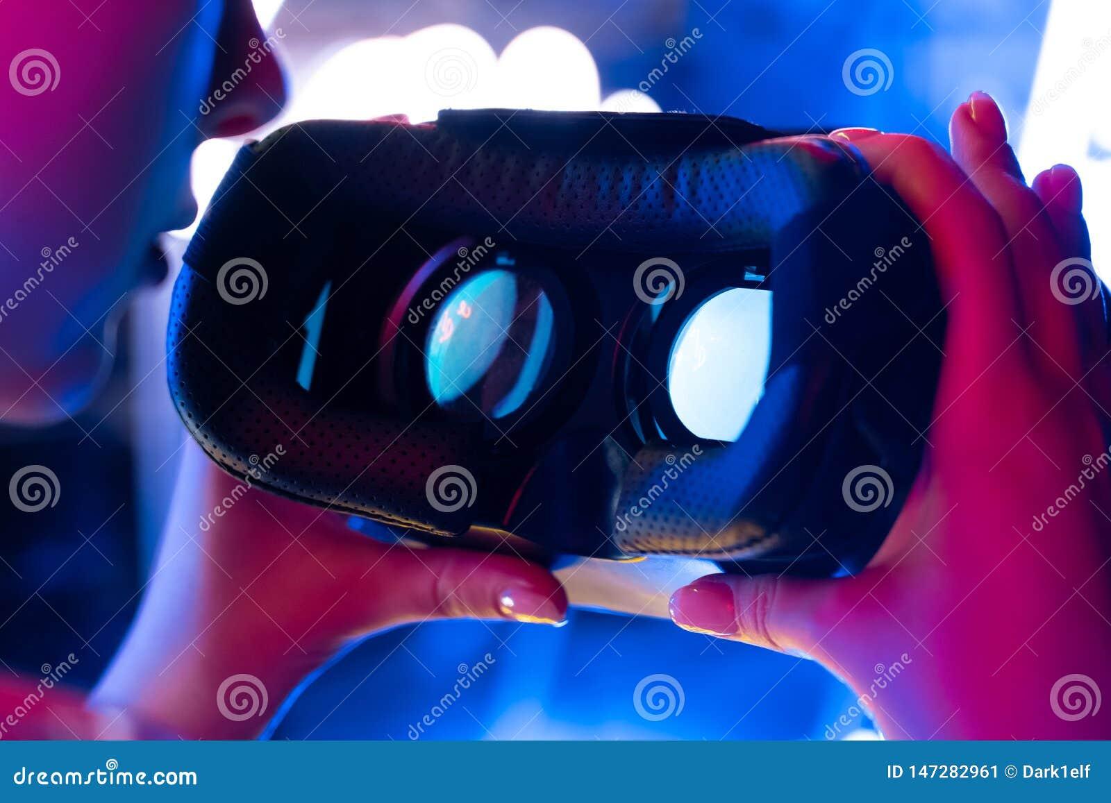 Les mains femelles tiennent des verres de casque du vr 3d 360 dans la lampe au néon futuriste, fin