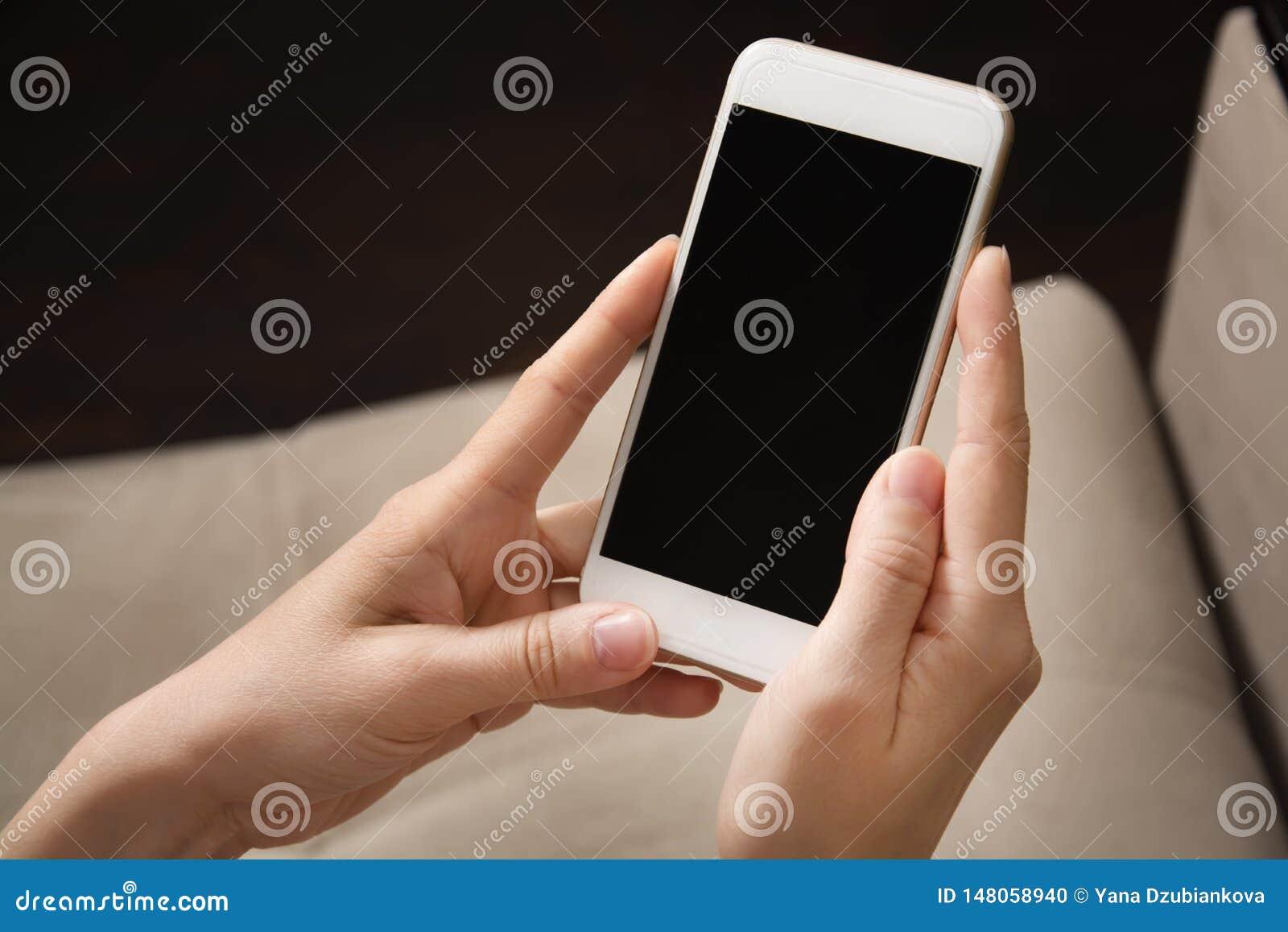 Les mains femelles tiennent le t?l?phone blanc dans leurs mains Plan rapproch? de t?l?phone portable
