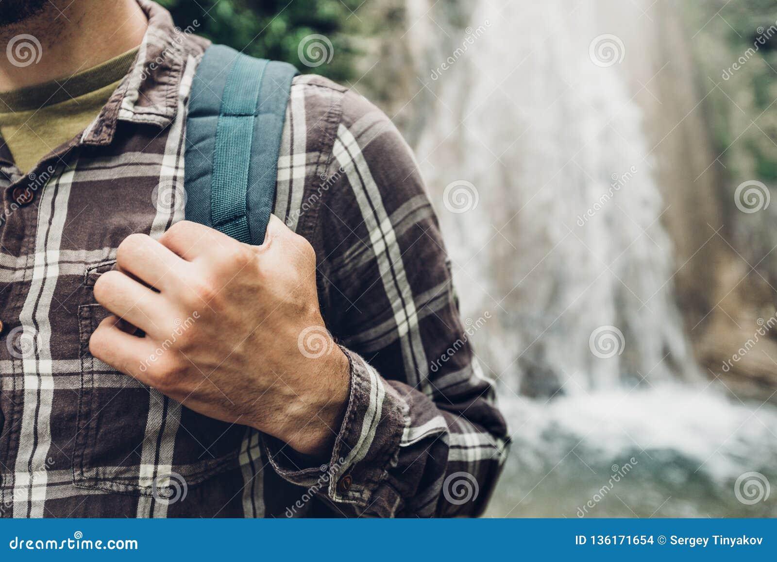 Les mains méconnaissables d homme de voyageur tient la courroie de sac à dos sur le fond de cascade augmentant le concept de voya