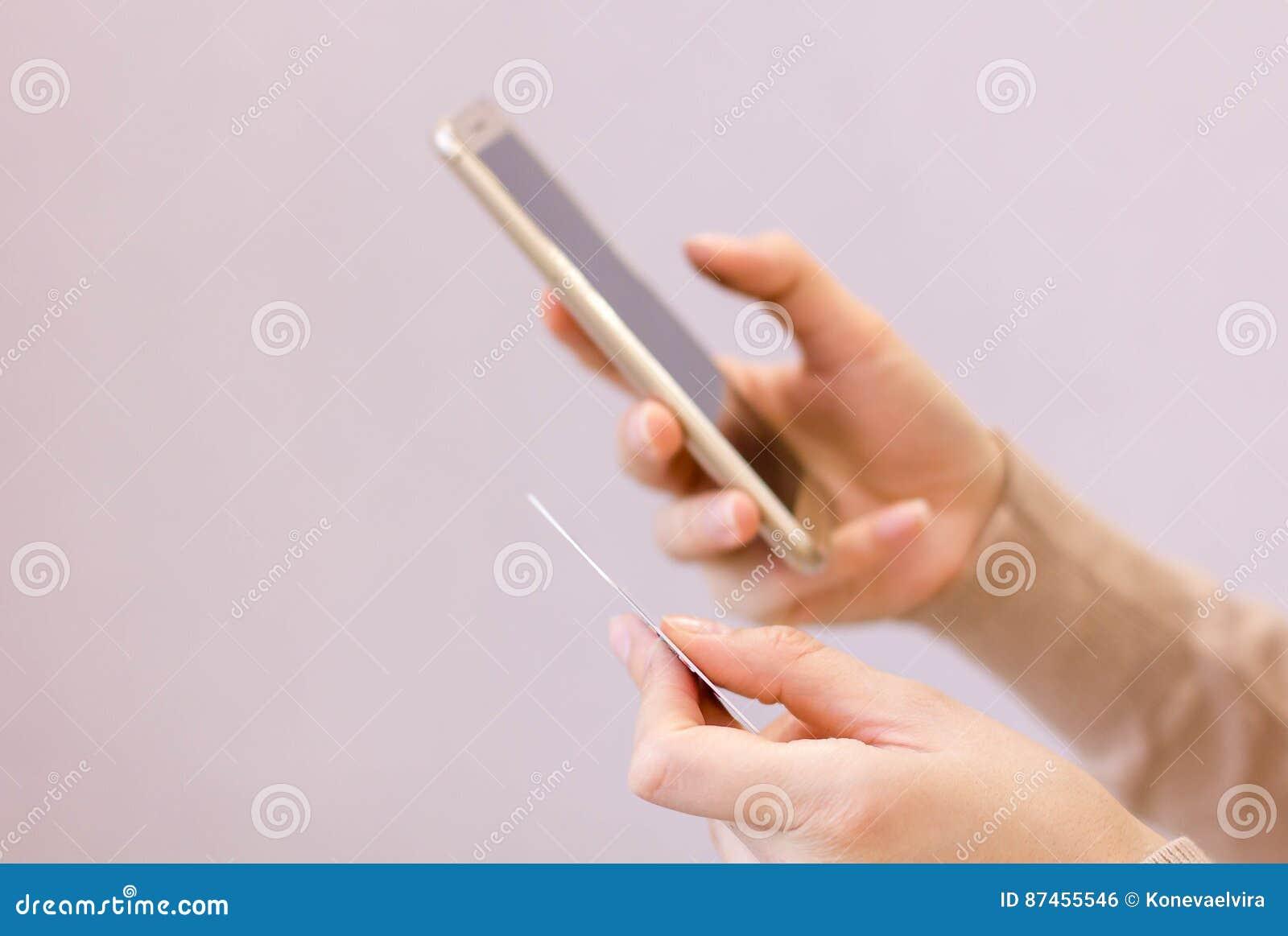 Les mains tenant la carte de crédit et se ferment vers le haut d utiliser le téléphone intelligent mobile avec le matin, achats e