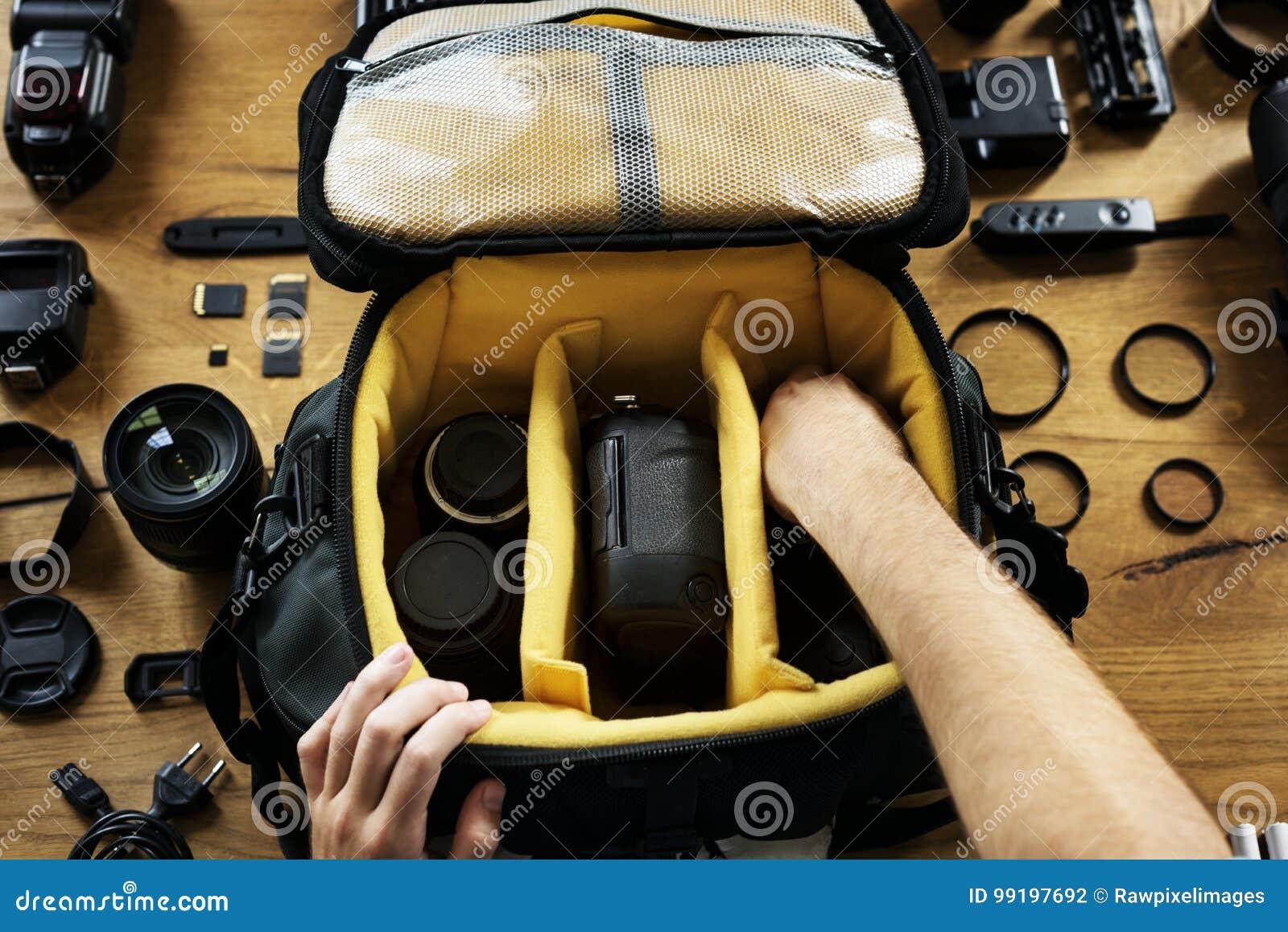 Les mains tenant une préparation de sac d appareil-photo ont mis un équipement dedans