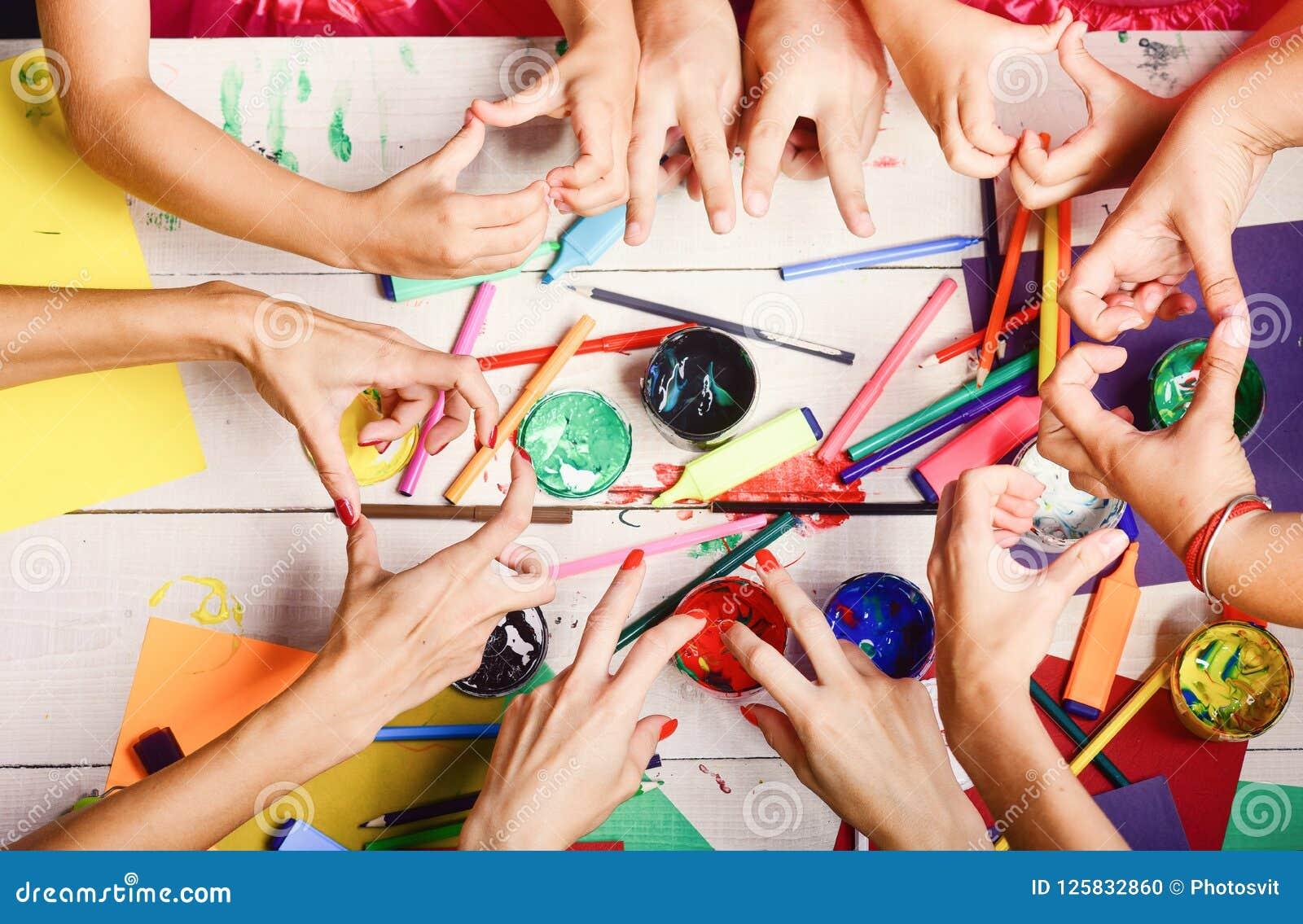 Les mains tiennent les marqueurs, les crayons et les peintures colorés Concept d art et de métier Mains d artistes avec la papete