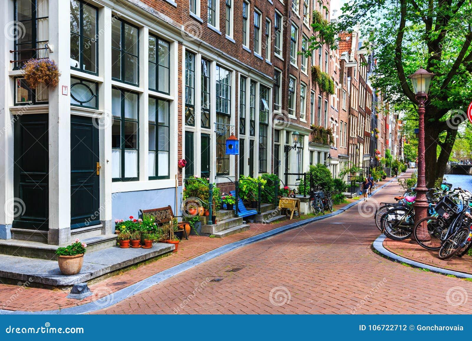 Les maisons néerlandaises traditionnelles, bicyclettes se sont garées sur la rue de ville à l été Architecture typique de la Holl