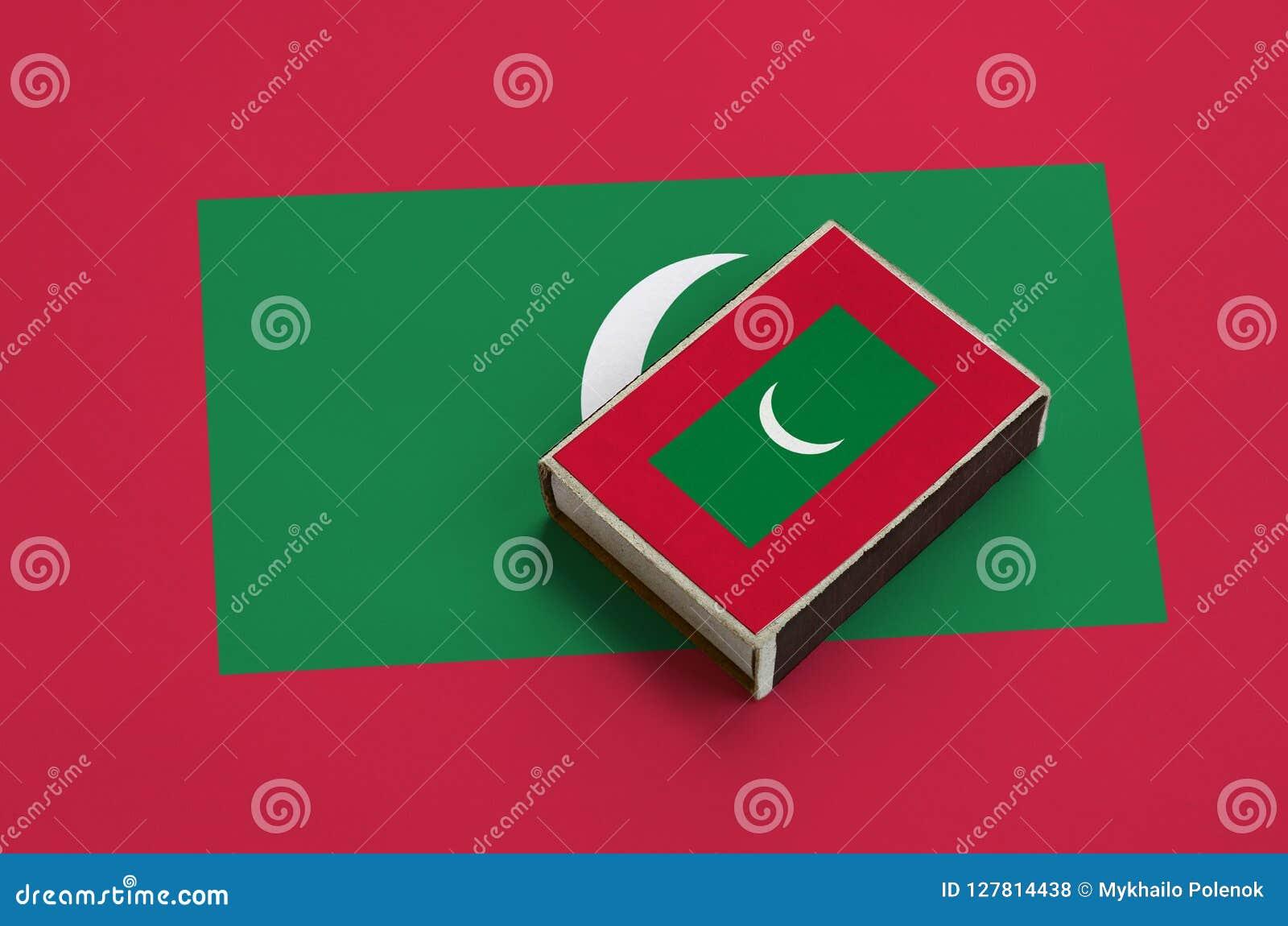 Les Maldives diminuent est décrites sur une boîte d allumettes qui se trouve sur un grand drapeau