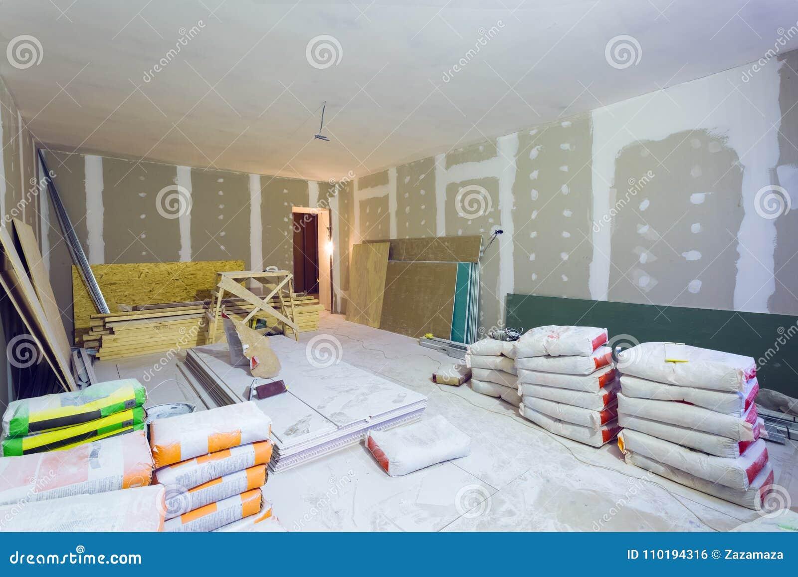 Les matériaux pour des paquets de mastic de construction, des feuilles de plaque de plâtre ou la cloison sèche en appartement est