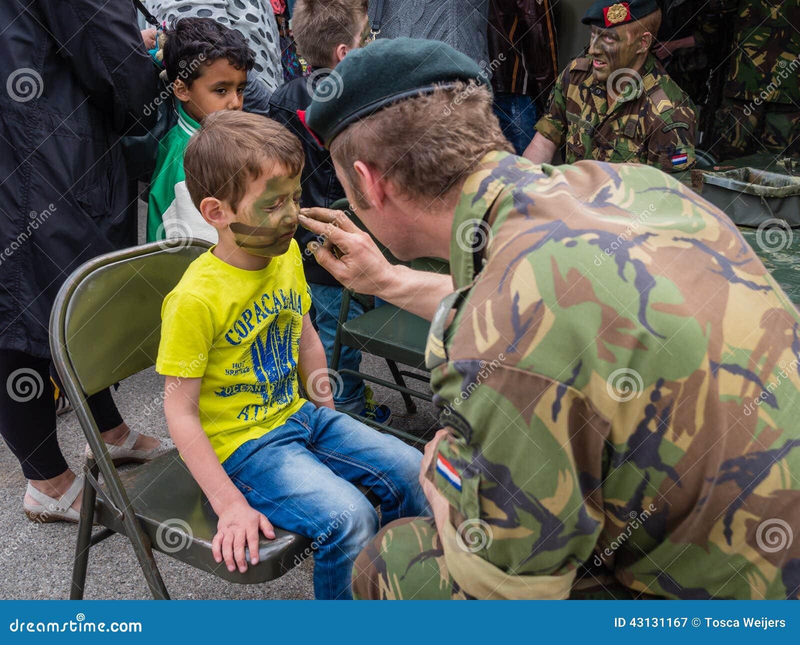 ALMERE, PAYS,BAS , 12 AVRIL 2014  Les enfants obtiennent le maquillage de  camouflage peint sur leurs visages par les militaires le jour national  d\u0027armée