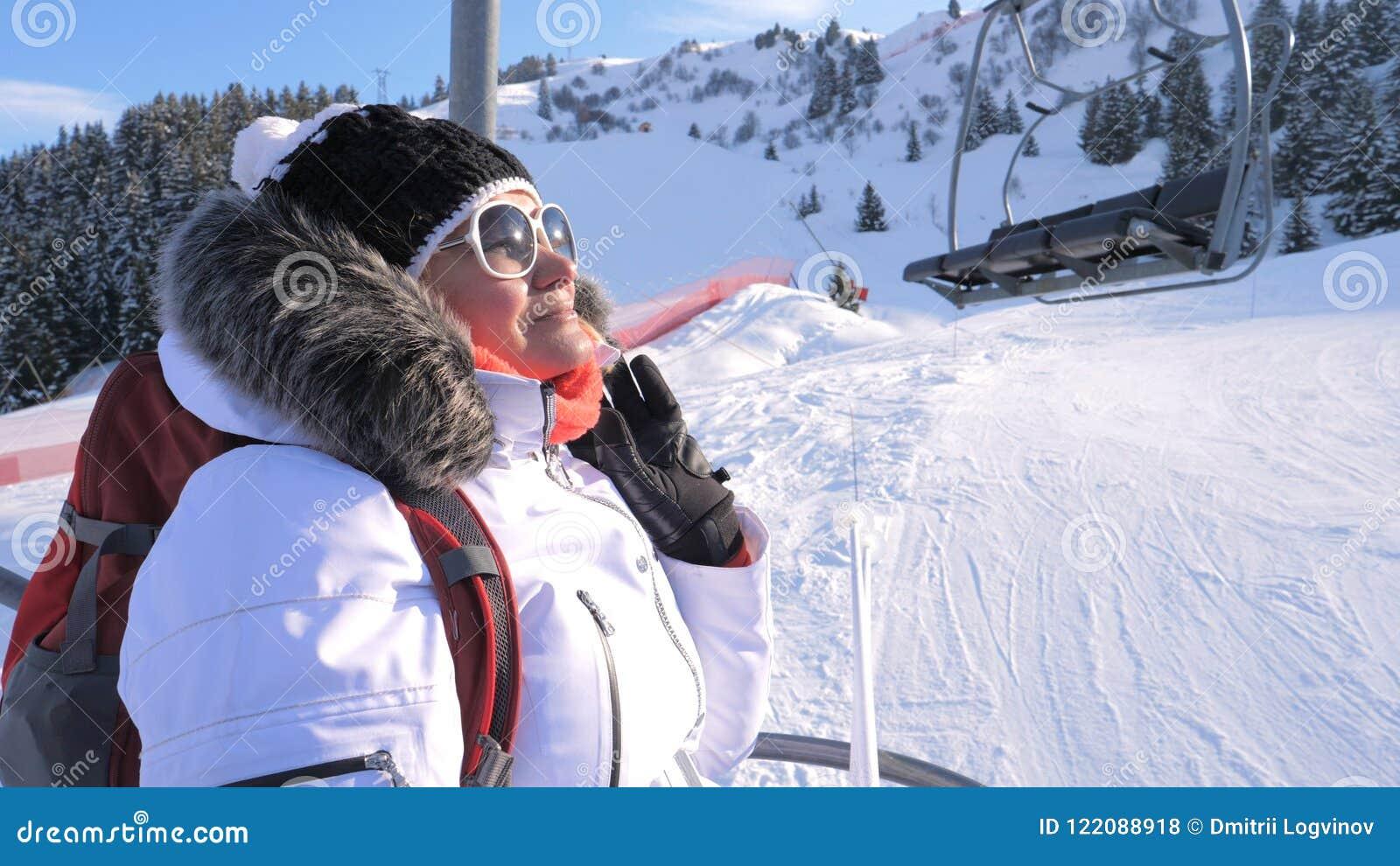 Les montées de skieur de femme une chaise soulèvent une montagne dans une station de sports d hiver