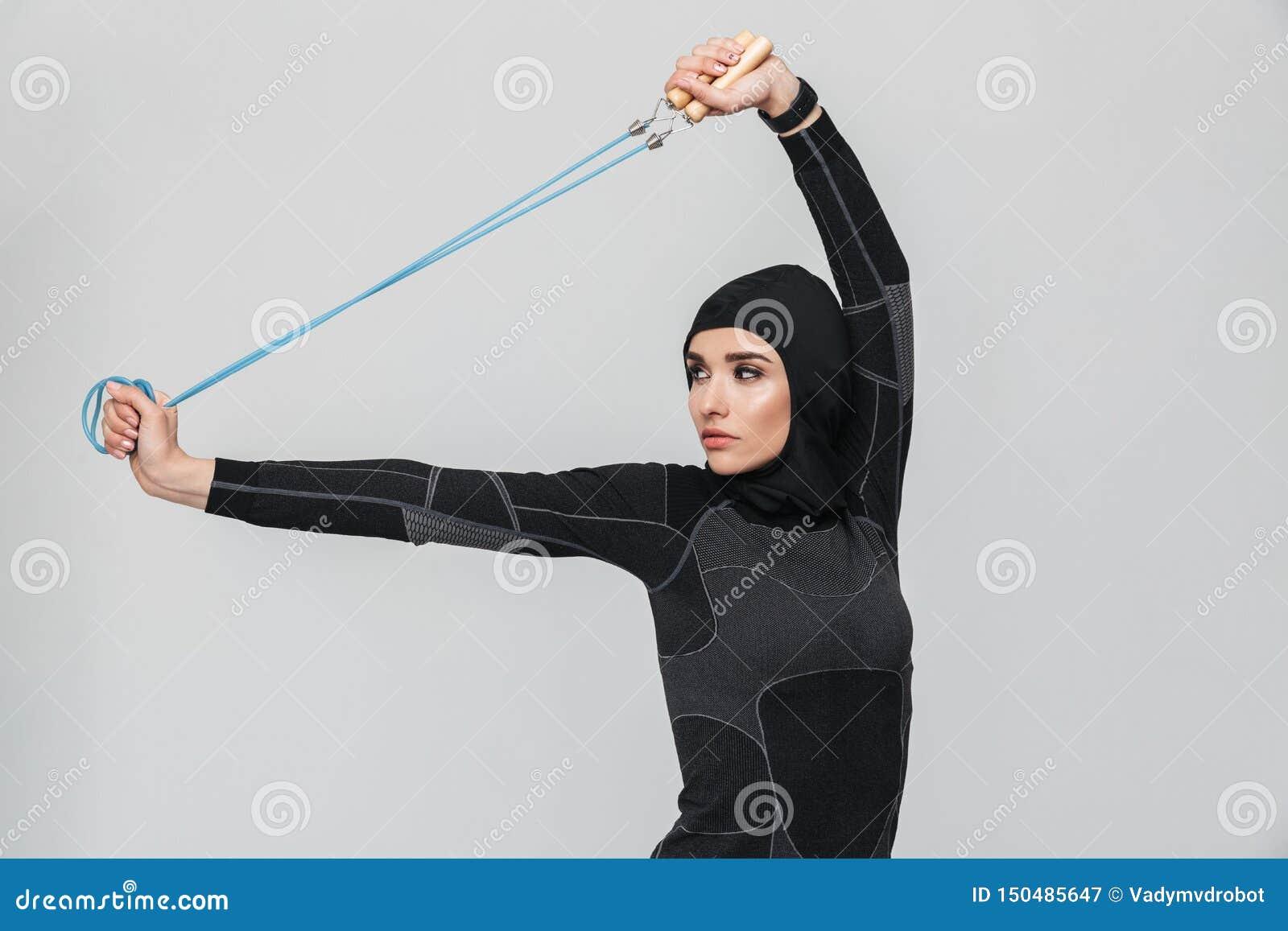 Les musulmans de forme physique de femme font des exercices avec la corde à sauter d isolement au-dessus du fond blanc de mur