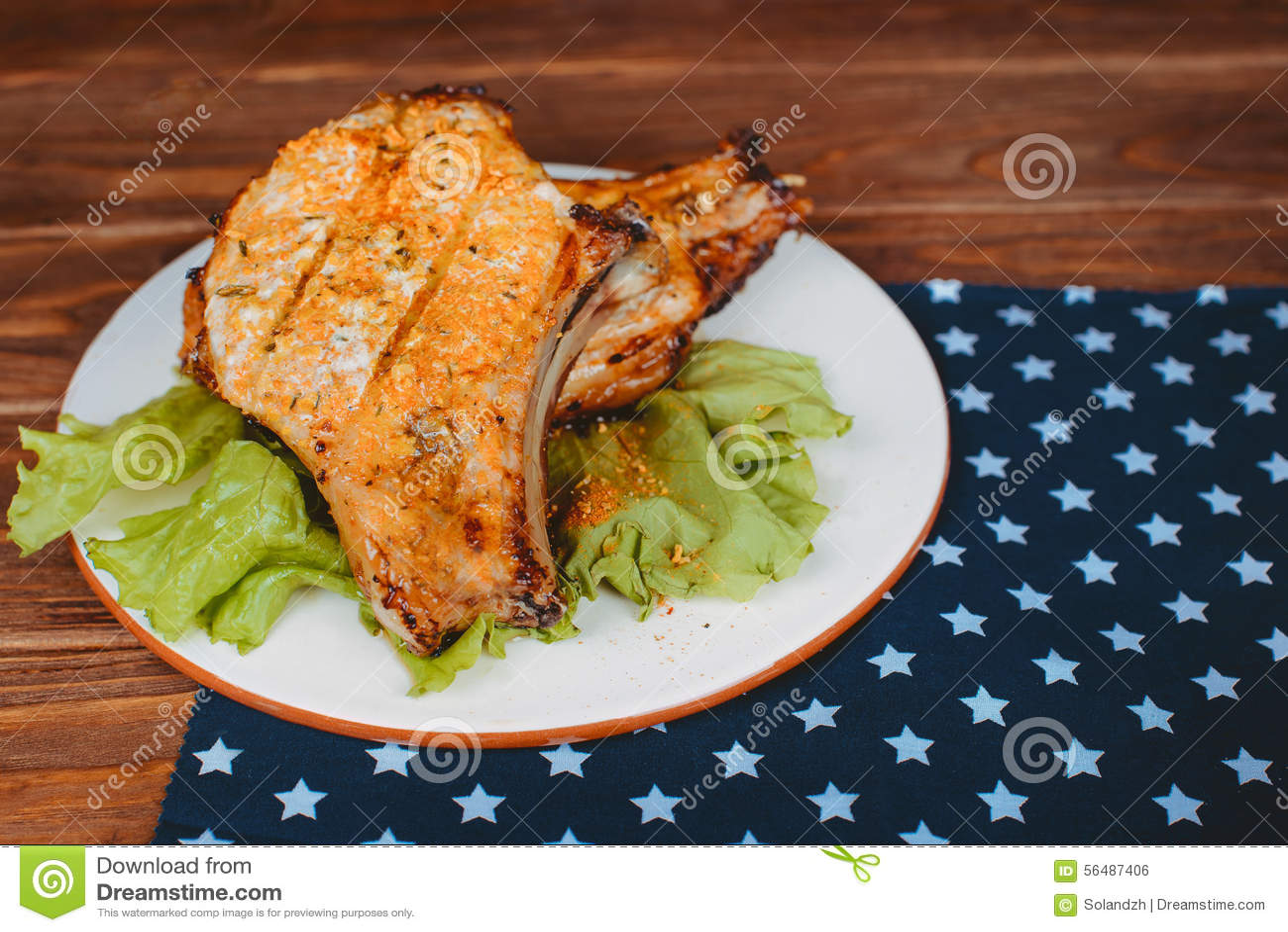 Les nervures de porc grillées tout entier délicieuses ont servi sur la laitue sur un vieux conseil en bois rustique