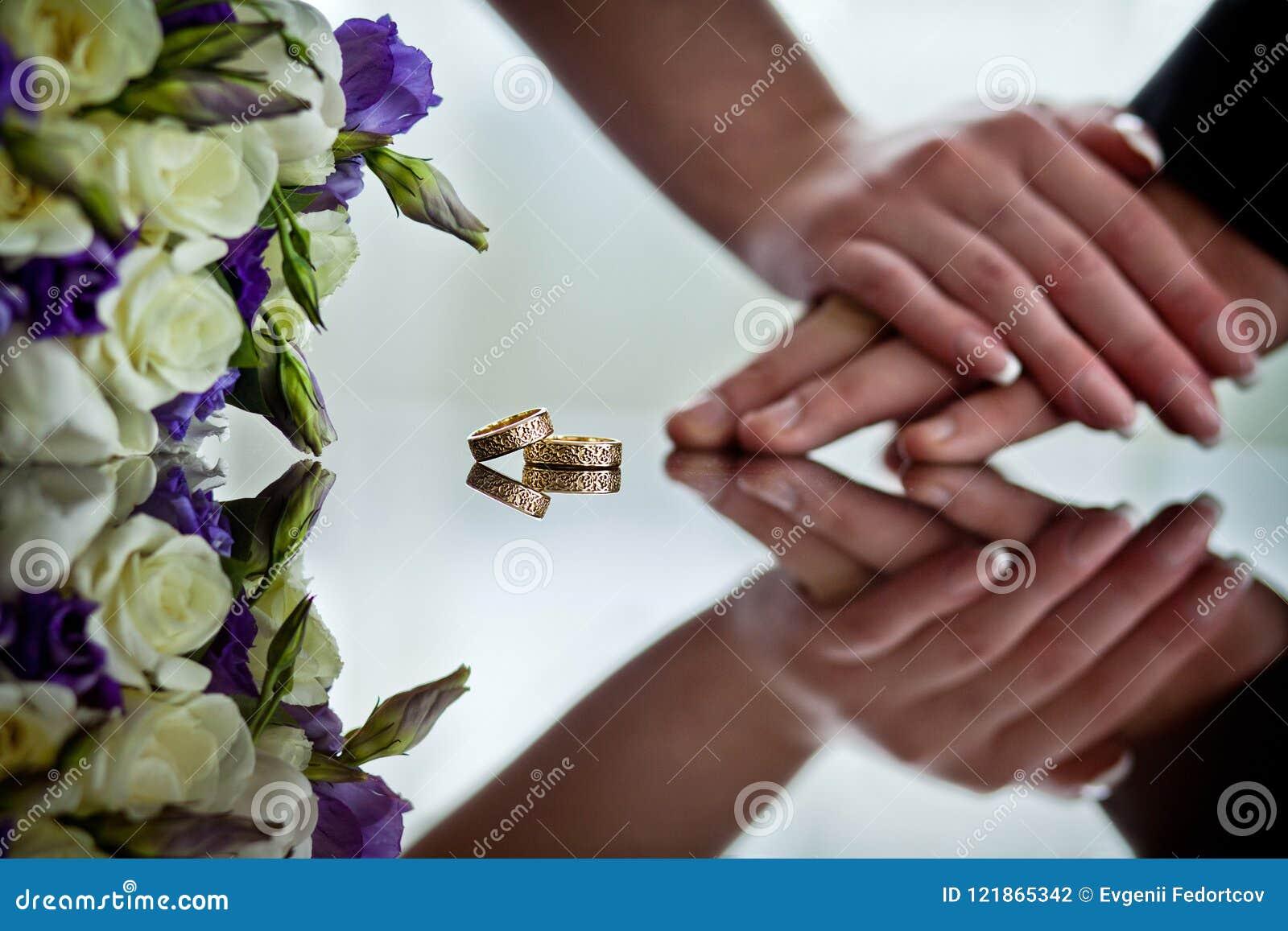 Les nouveaux mariés tiennent des mains à côté des anneaux de mariage qui se trouvent sur la surface de miroir