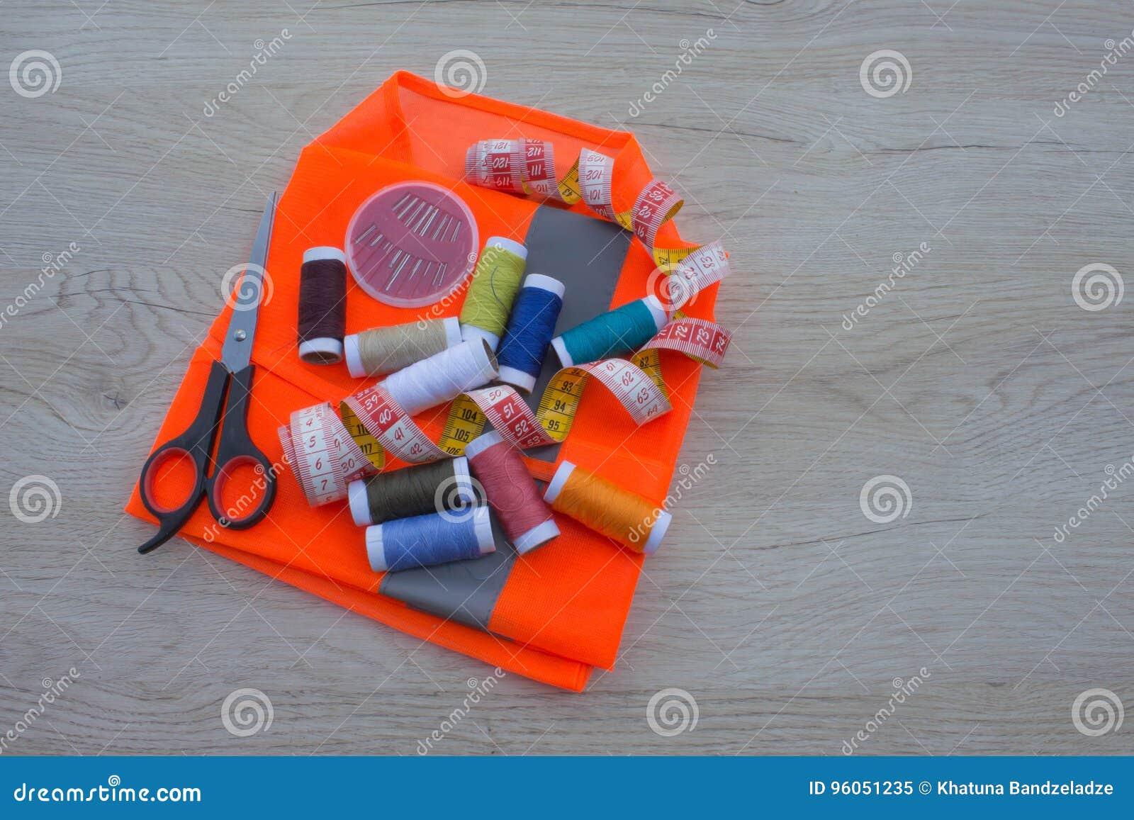 Les outils pour coudre pour le passe-temps ont placé sur la vue supérieure de fond en bois de table Fil, aiguilles et tissu
