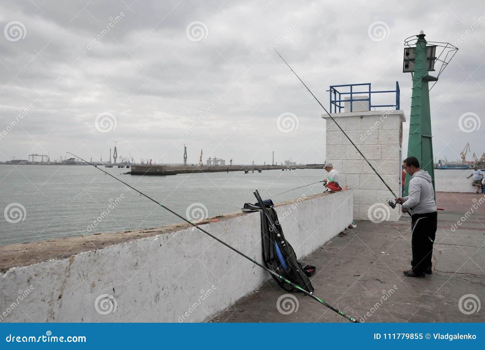 Les pêcheurs pêchent dans le port du port maritime de Cadix