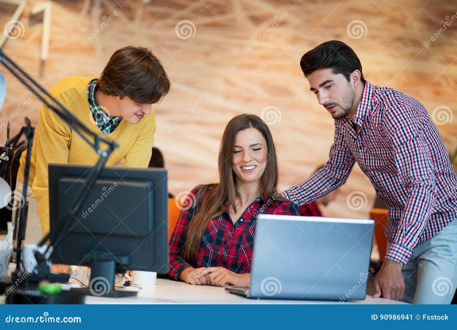 Les personnes de jeune entreprise groupent le travail comme équipe