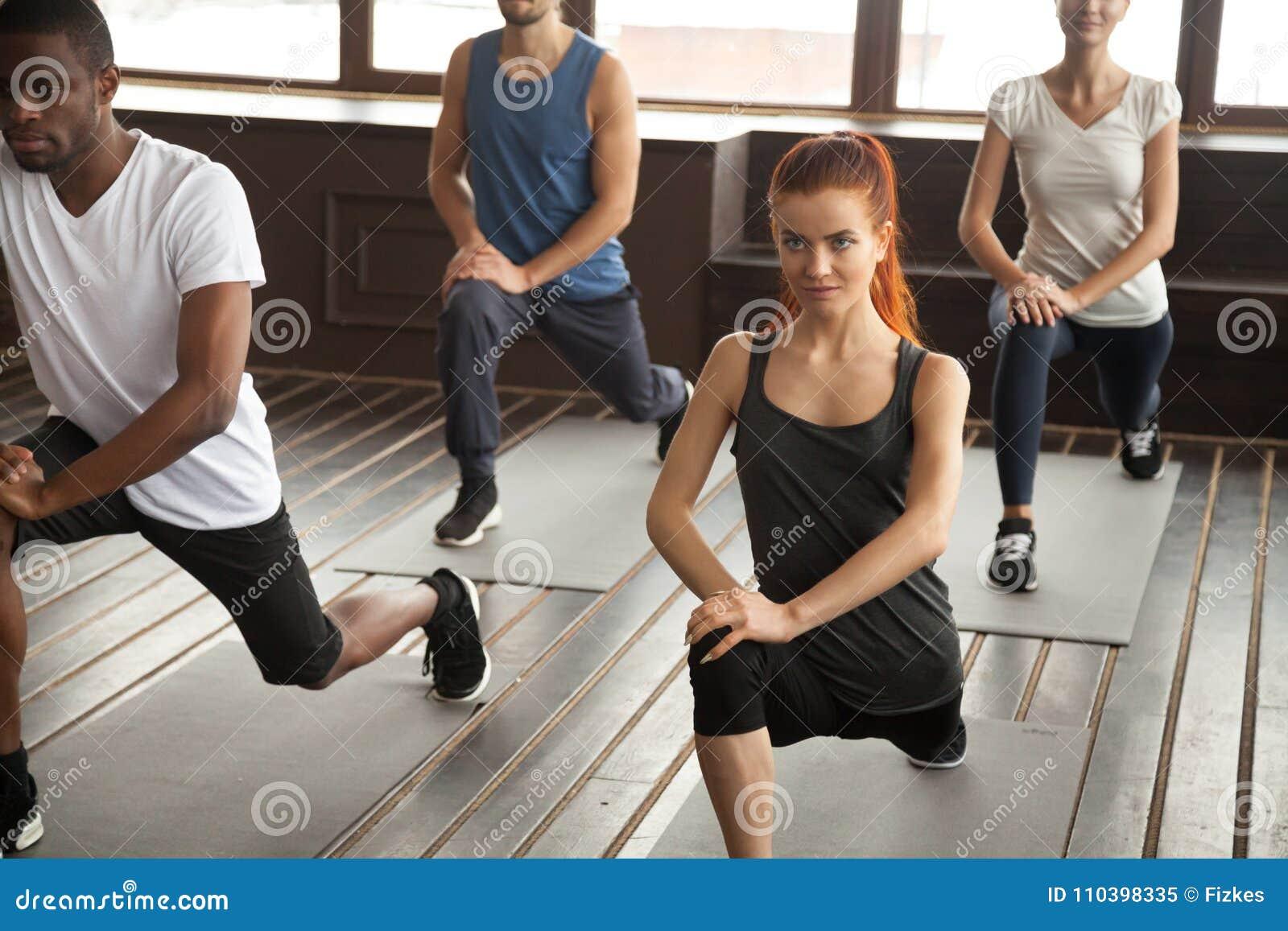 Les personnes diverses sportives faisant le mouvement brusque s exercent en avant au trai de groupe