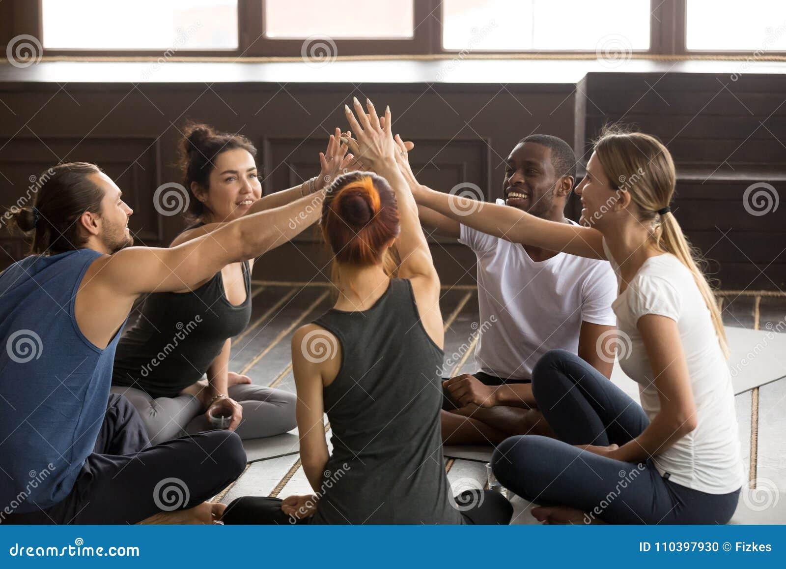 Les personnes heureuses diverses de yogi atteignent des mains pour donner la haute cinq