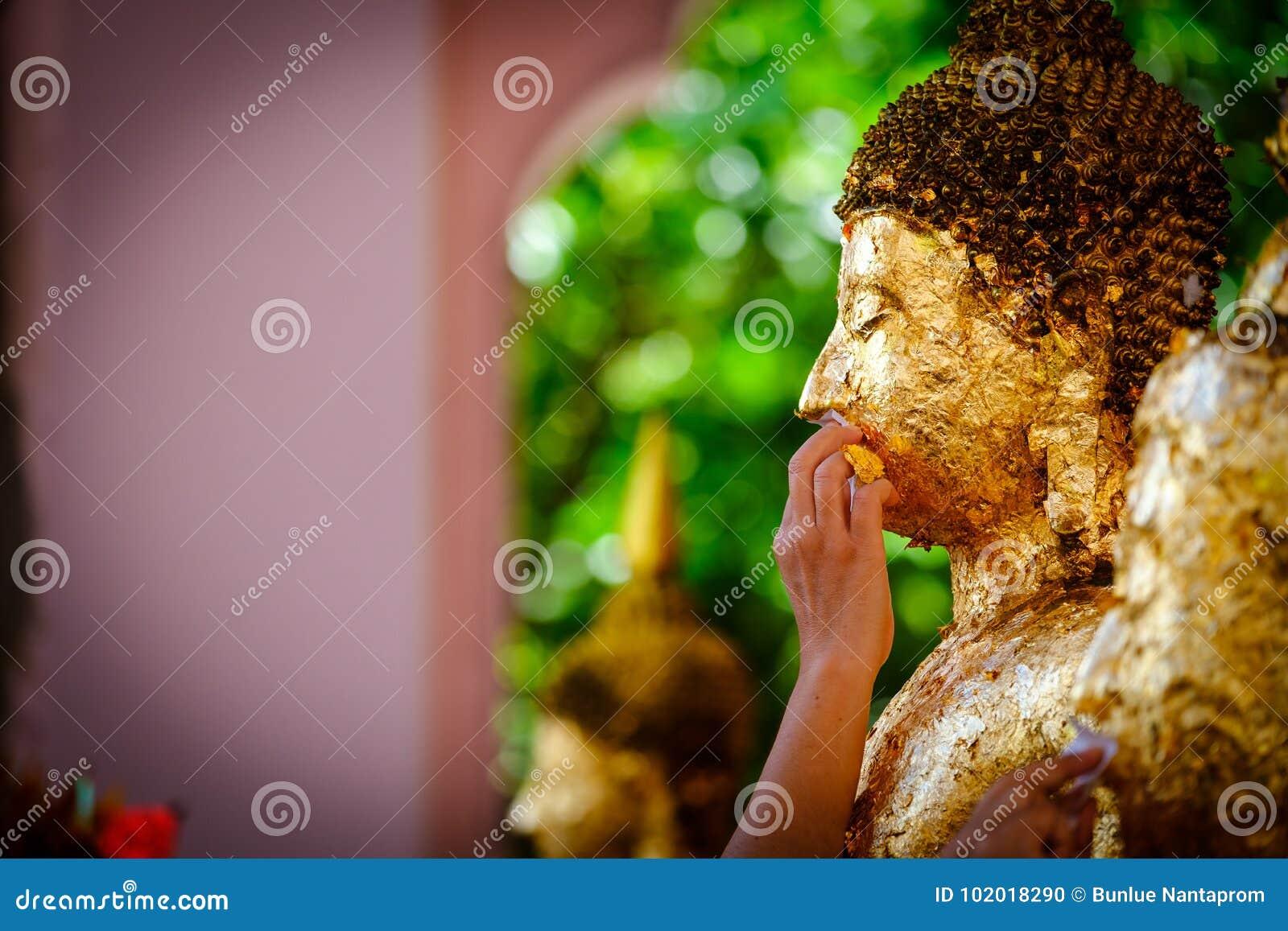 Les personnes thaïlandaises font le mérite, bouddhistes dorant la feuille d or sur le visage