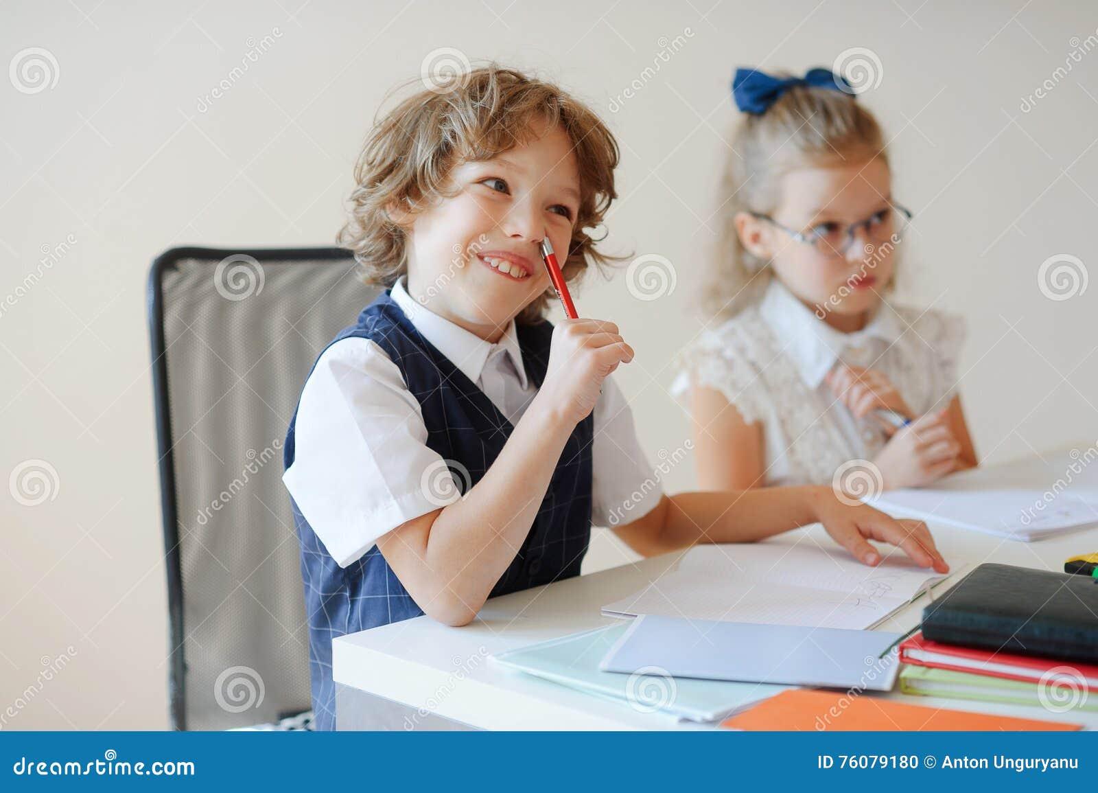 Les petits élèves drôles se reposent à un bureau