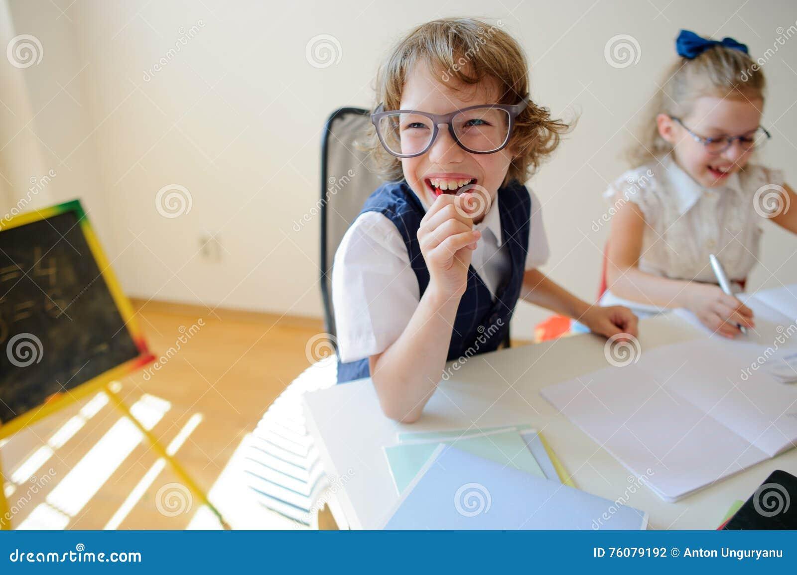 Les petits étudiants ridicules à lunettes, le garçon et la fille, partagent le même bureau