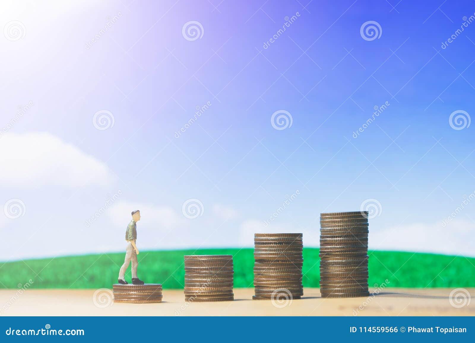 Les petits chiffres homme d affaires de personnes miniatures marchant sur l argent de la pile de pièce de monnaie intensifient la