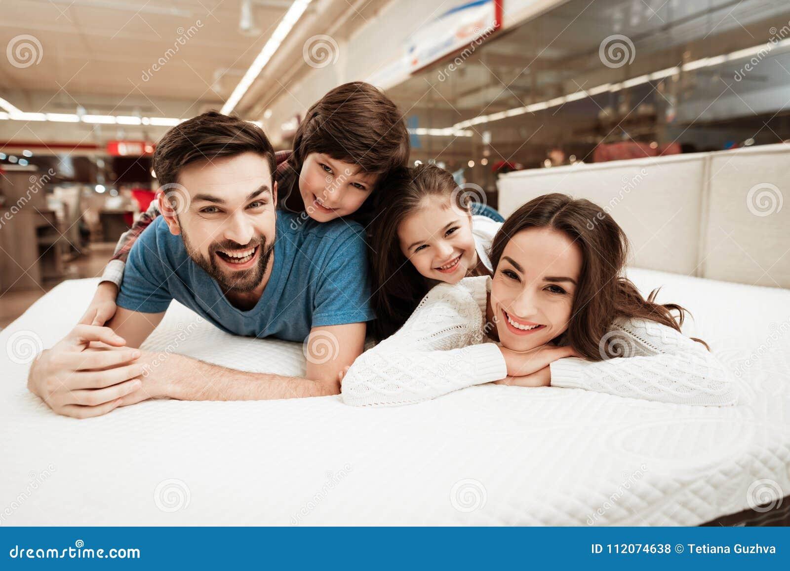 Les petits enfants se trouvent sur les dos de jeunes parents heureux dans un magasin de matelas